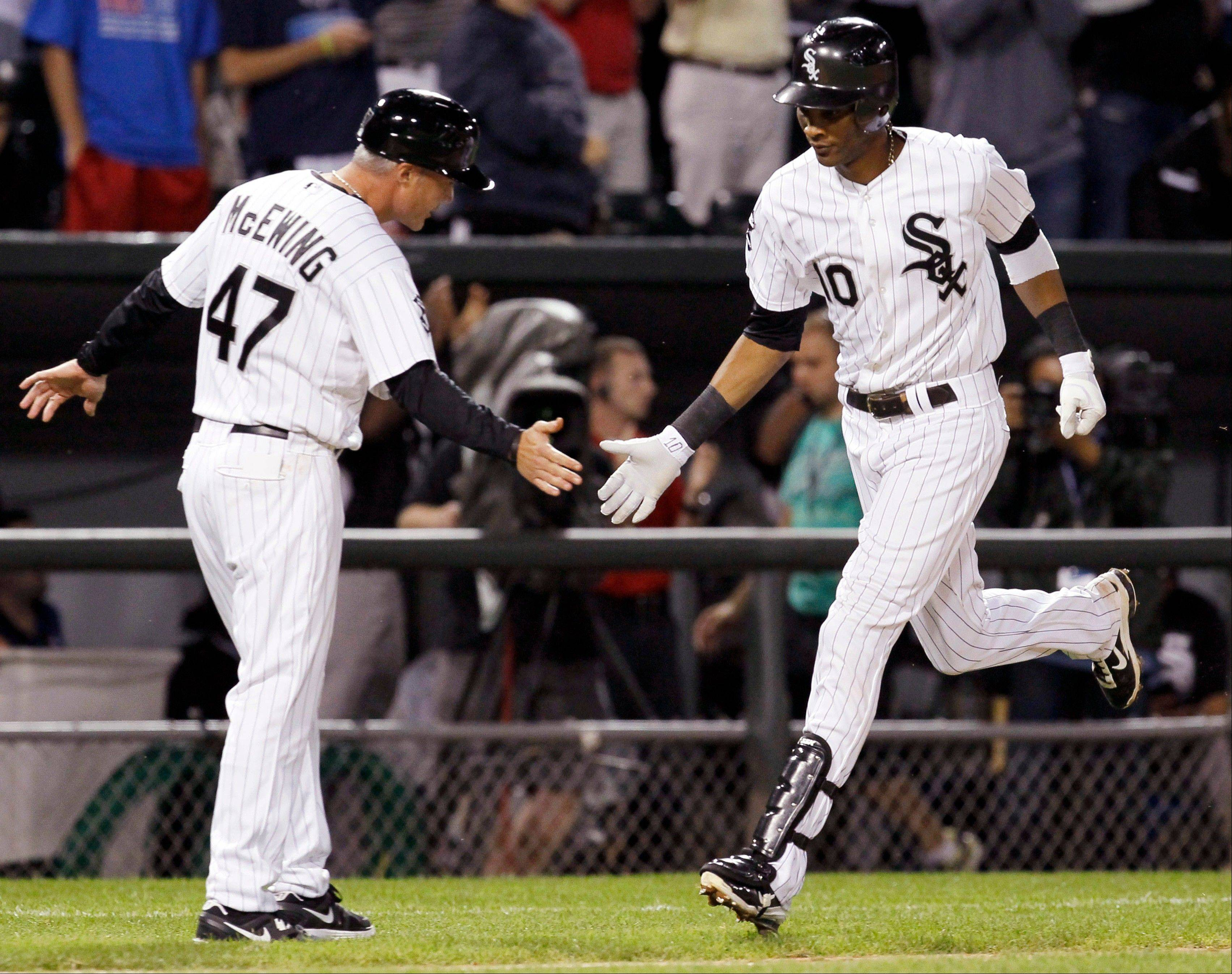 Chicago White Sox's Alexei Ramirez, right, is greeted by third base coach Joe McEwing after hitting a two-run home run off New York Yankees relief pitcher Boone Logan, also scoring A.J. Pierzynski, during the seventh inning of a baseball game, Monday in Chicago.