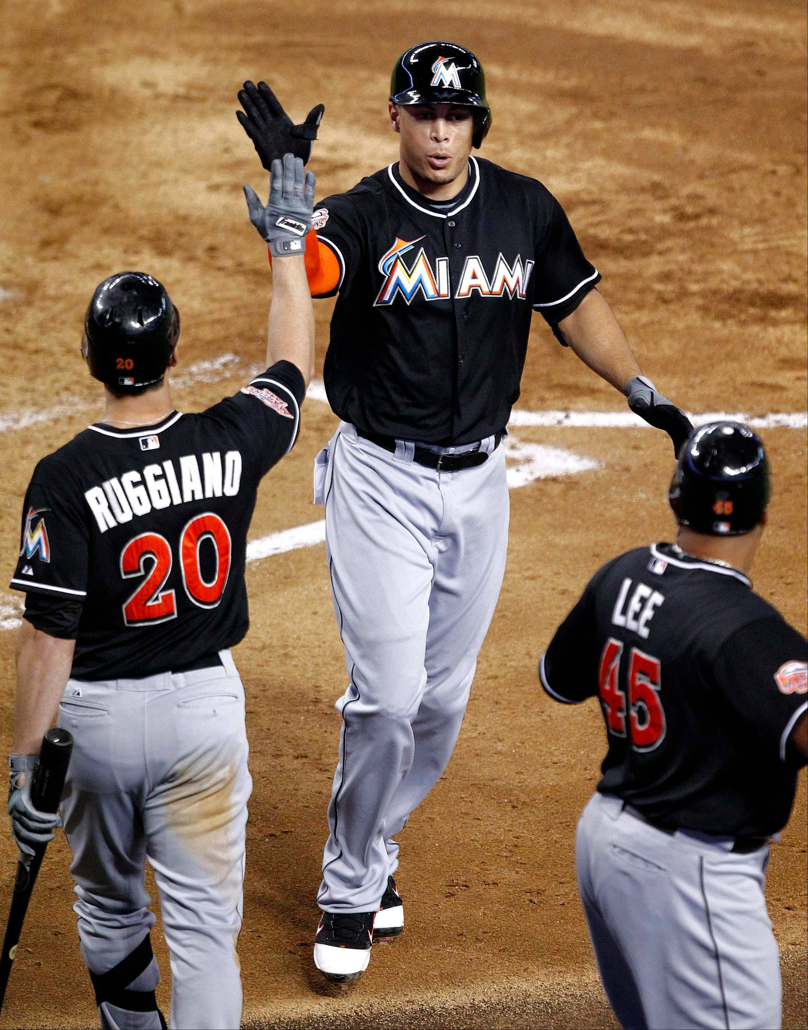 The Marlins' Giancarlo Stanton is greeted at home plate by teammate Justin Ruggiano and Carlos Lee after hitting a three-run home run against the Arizona Diamondbacks during the fourth inning Monday in Phoenix.