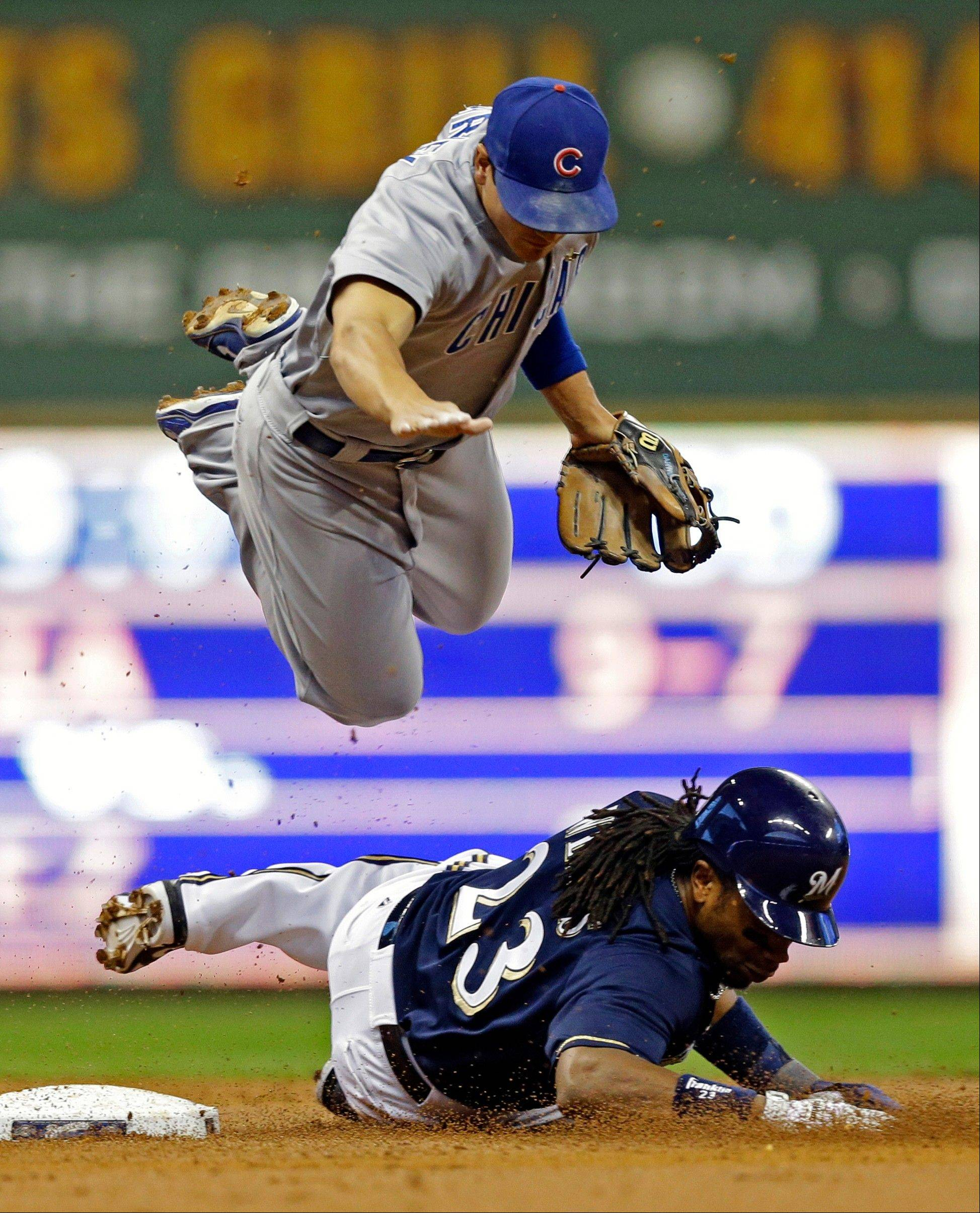 Chicago Cubs' Darwin Barney, top, is upended as he forces out Milwaukee Brewers' Rickie Weeks at second base and throws on to first base for a double play on Brewers' Ryan Braun during the first inning of a baseball game Monday in Milwaukee.