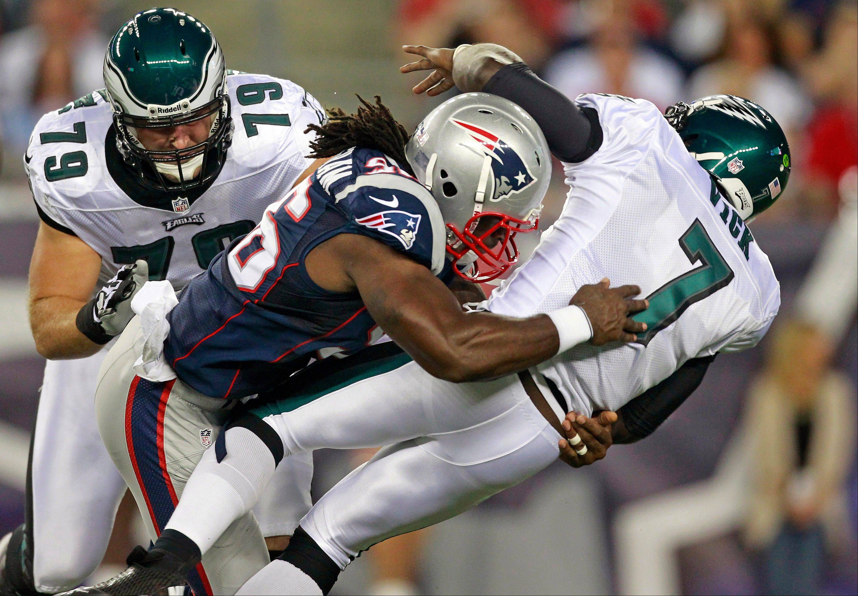 New England Patriots linebacker Jermaine Cunningham (96) drops Philadelphia Eagles quarterback Michael Vick (7) to the field on a hard hit during the first quarter of an NFL preseason football game Monday night in Foxborough, Mass. Vick left the game after the play. At left is Philadelphia Eagles tackle Todd Herremans.