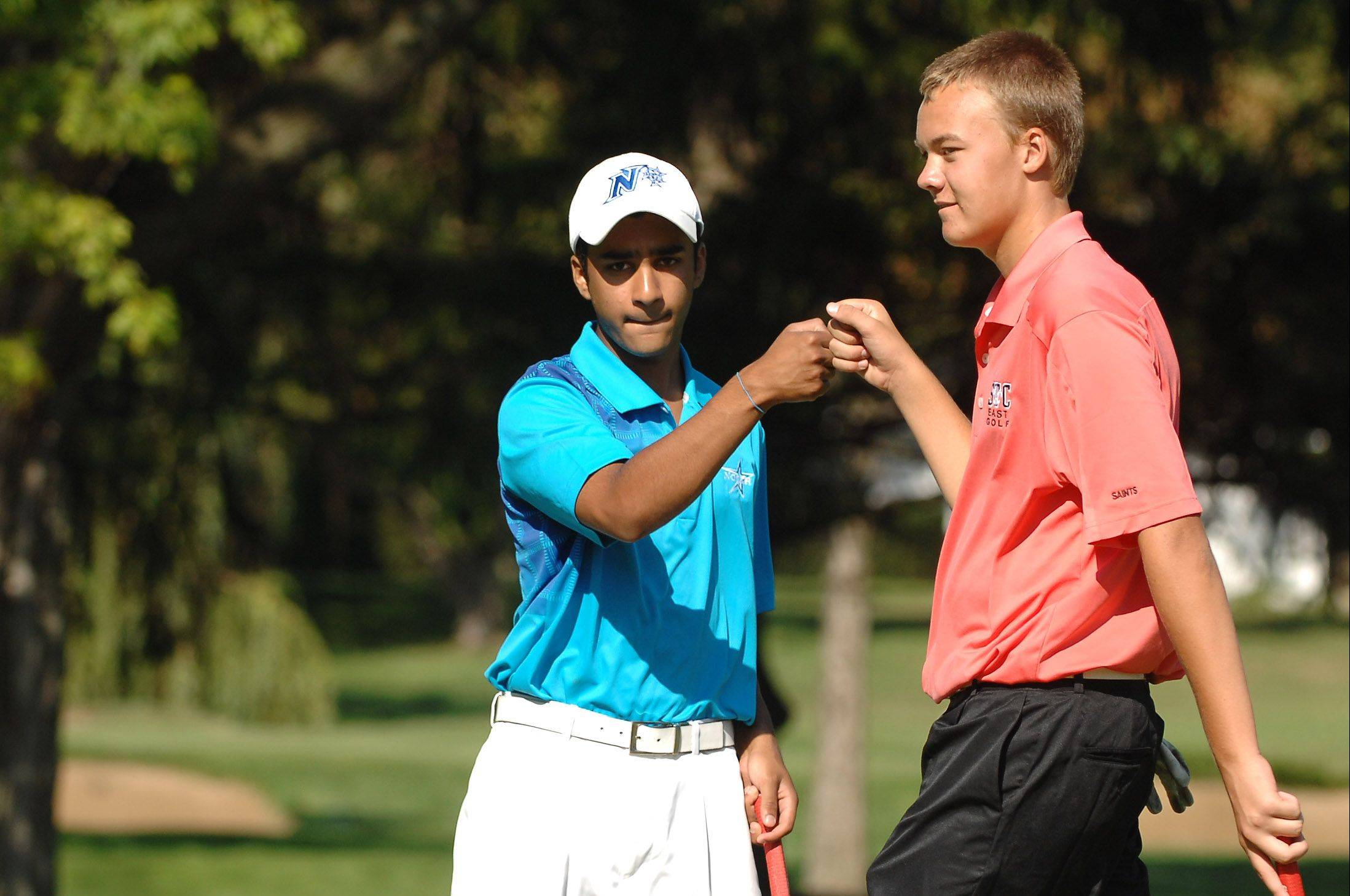 St. Charles North's Raghav Cherala gets a fist bump from teammate Mick Vyzral of St. Charles East after sinking a putt.