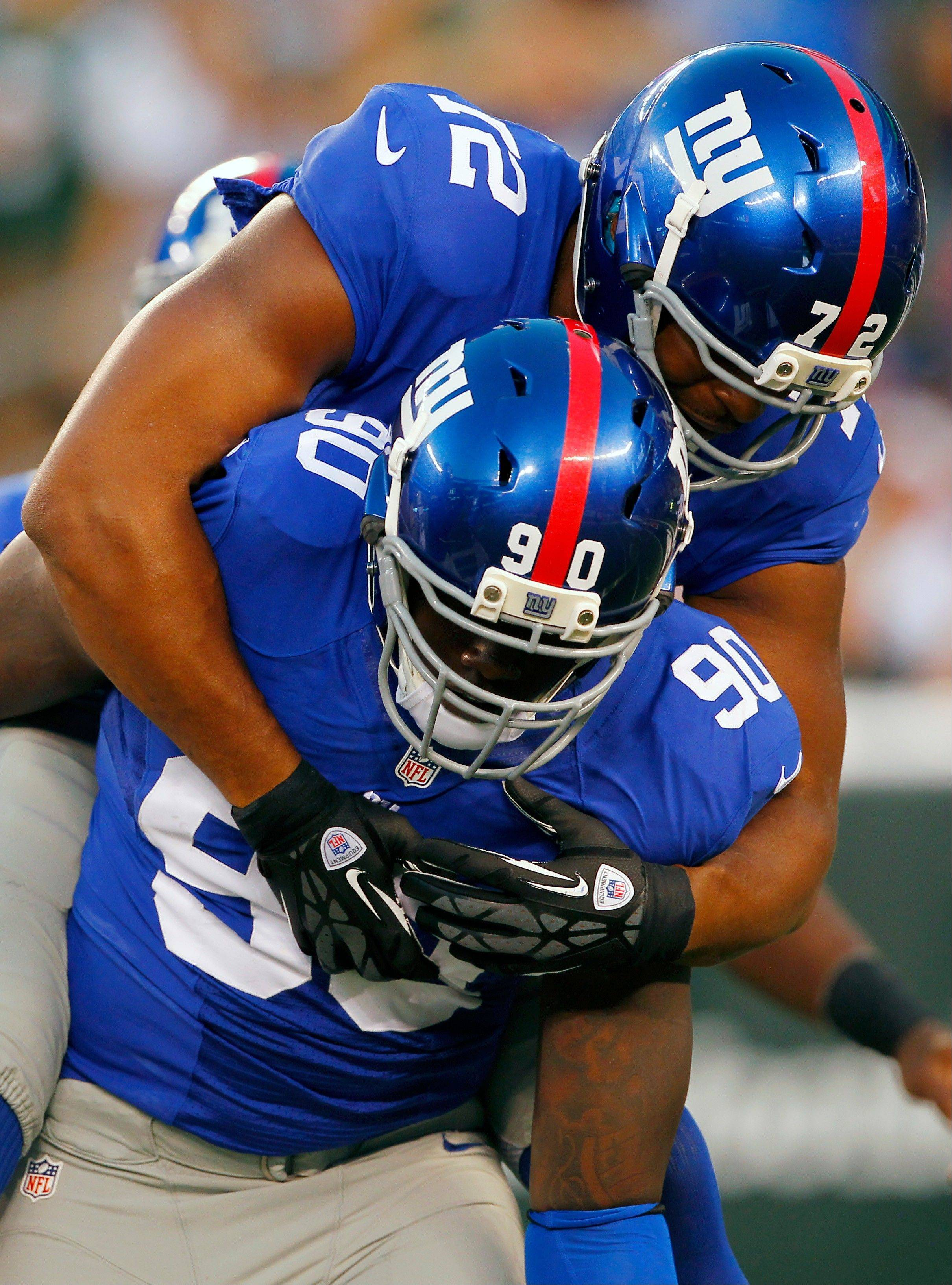Giants defensive end Jason Pierre-Paul (90) reacts with teammate Osi Umenyiora (72) after sacking Jets quarterback Mark Sanchez in Saturday's preseason game.
