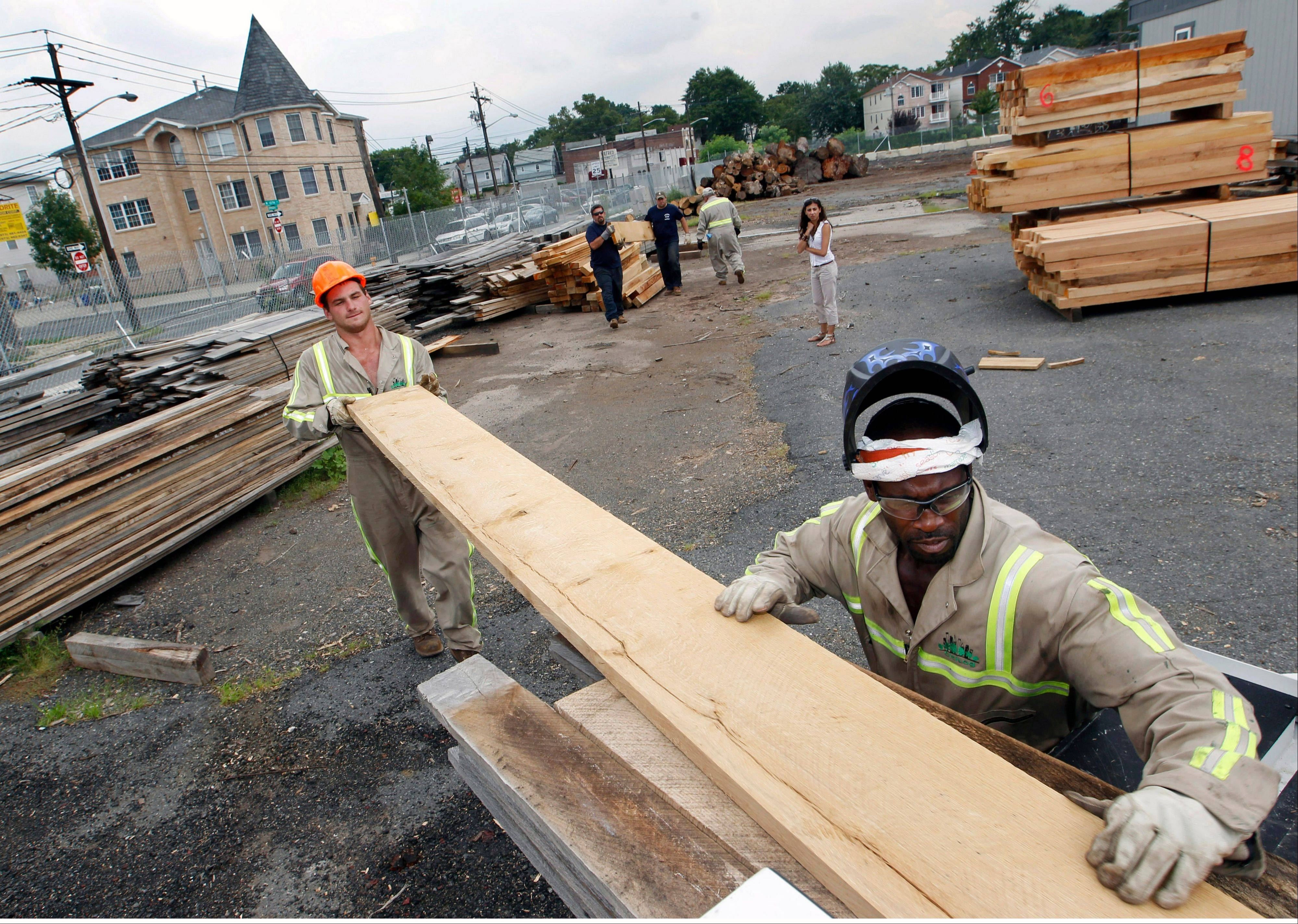 Workers Wiil Warmbold, left, and Charles Davidson load wood planks recently cut from discarded tree trunks into a truck for the town of Secaucus, N.J., at Citilog in Newark, N.J.