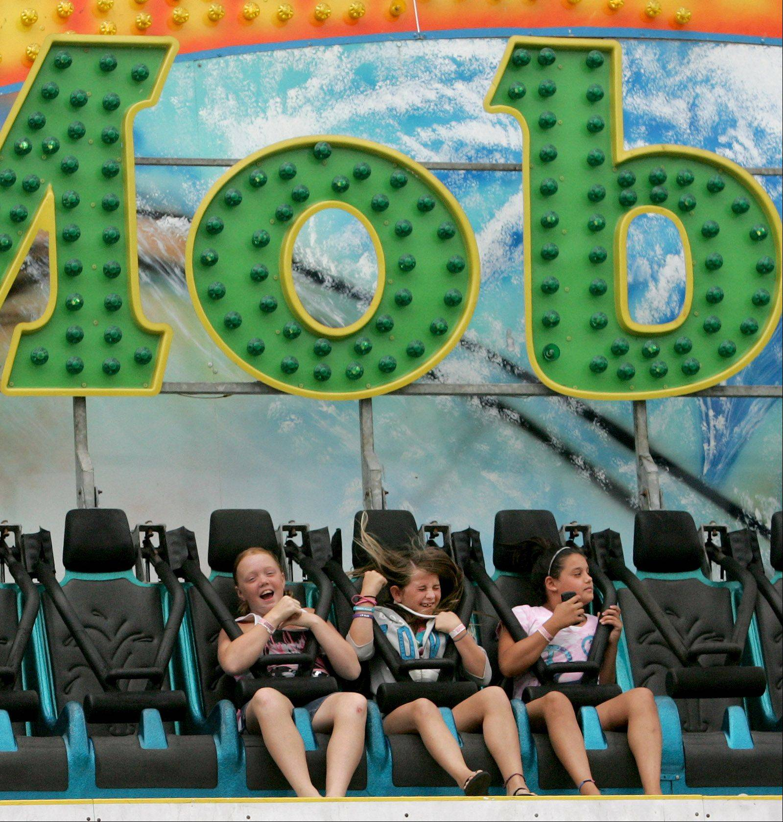 Left to right, Jessica Cox, 10, Erin Miller, 11 and Annamarie Petrella, 11, of Wood Dale, take a turn on the Moby Dick carnival ride during Wood Dale Prairie Fest at Town Center on Sunday.