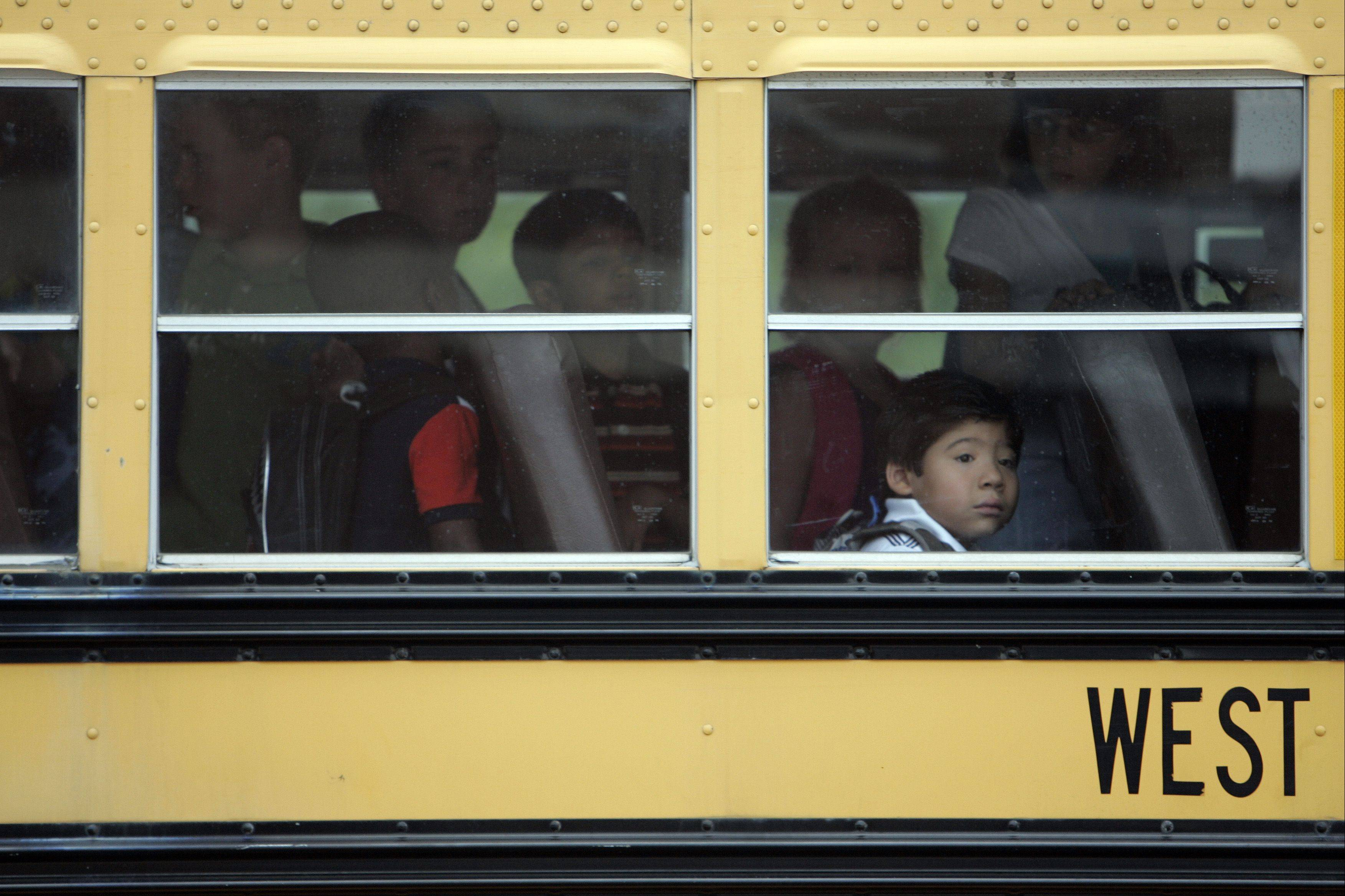 Seven-year-old Gabriel Morales waits patiently to get off the school bus for first grade during the first day of school at Fearn Elementary School in North Aurora Wednesday August 15, 2012.