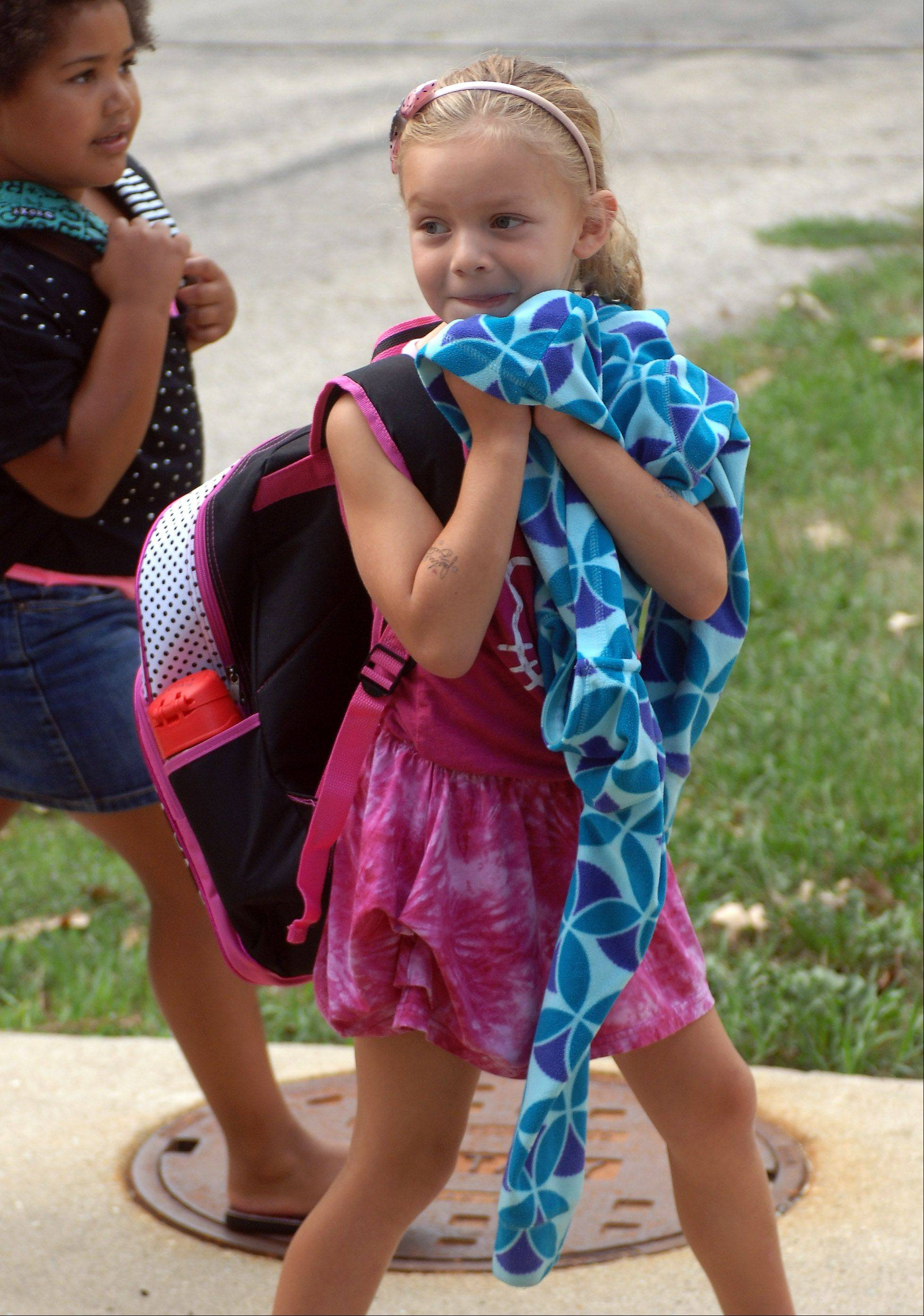 First day of classes were held Wednesday at the Wauconda Community Unit School District 118 schools. First grade student Hannah Phillips cracks a little smile as she heads into Robert Crown School.