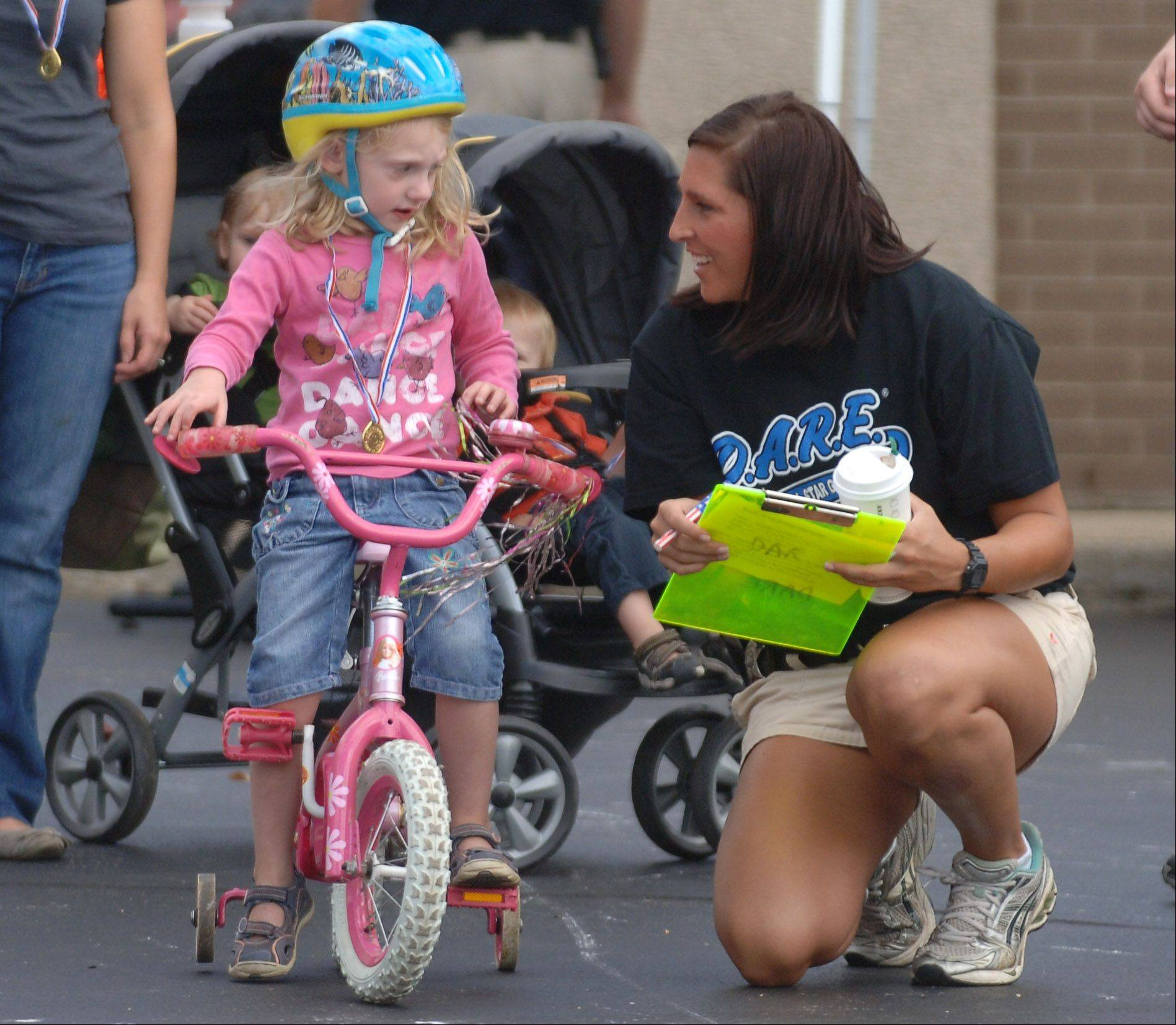 Gurnee police officer Dana Dingman, right, gives instructions to 4-year-old Reese Warwick of Gurnee during the Gurnee Days annual Bike Rodeo Friday at the Gurnee Fire Station #1. Gurnee Days activities continue through Sunday.