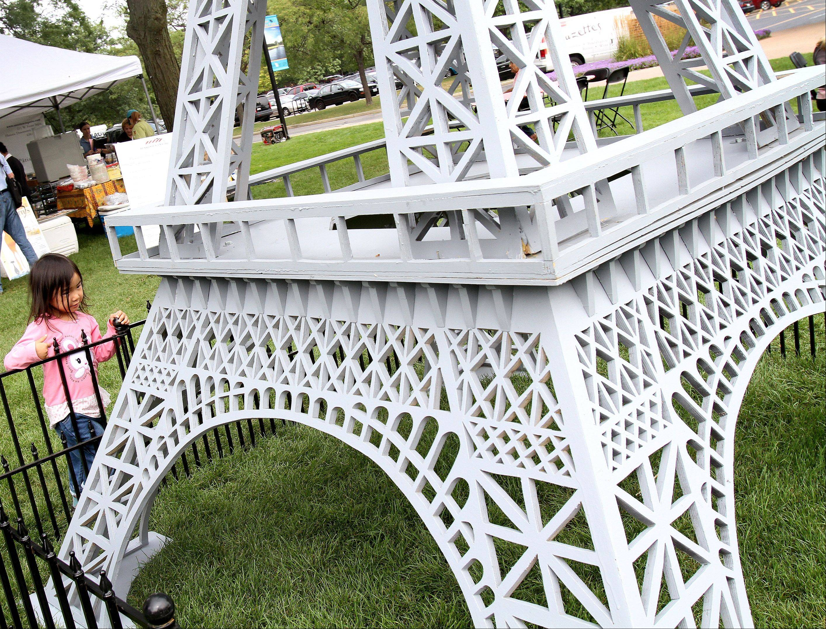 Jasmine Su, 4, of Bartlett, checks out a mini Eiffel Tower on display for French Connection Day at Cantigny Park in Wheaton on Sunday.