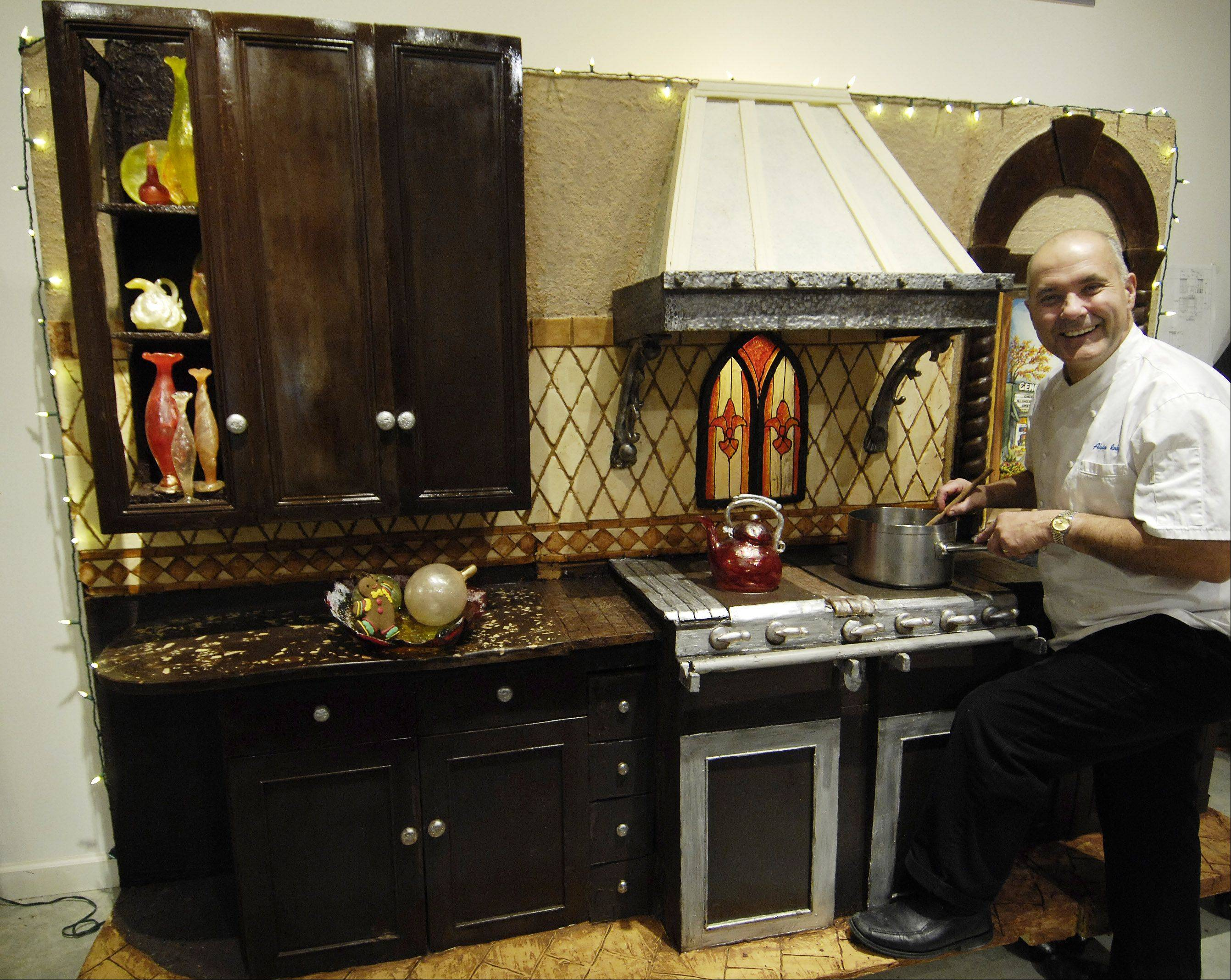 Chef Alain Roby poses with his life-size chocolate kitchen in his downtown Geneva kitchen.