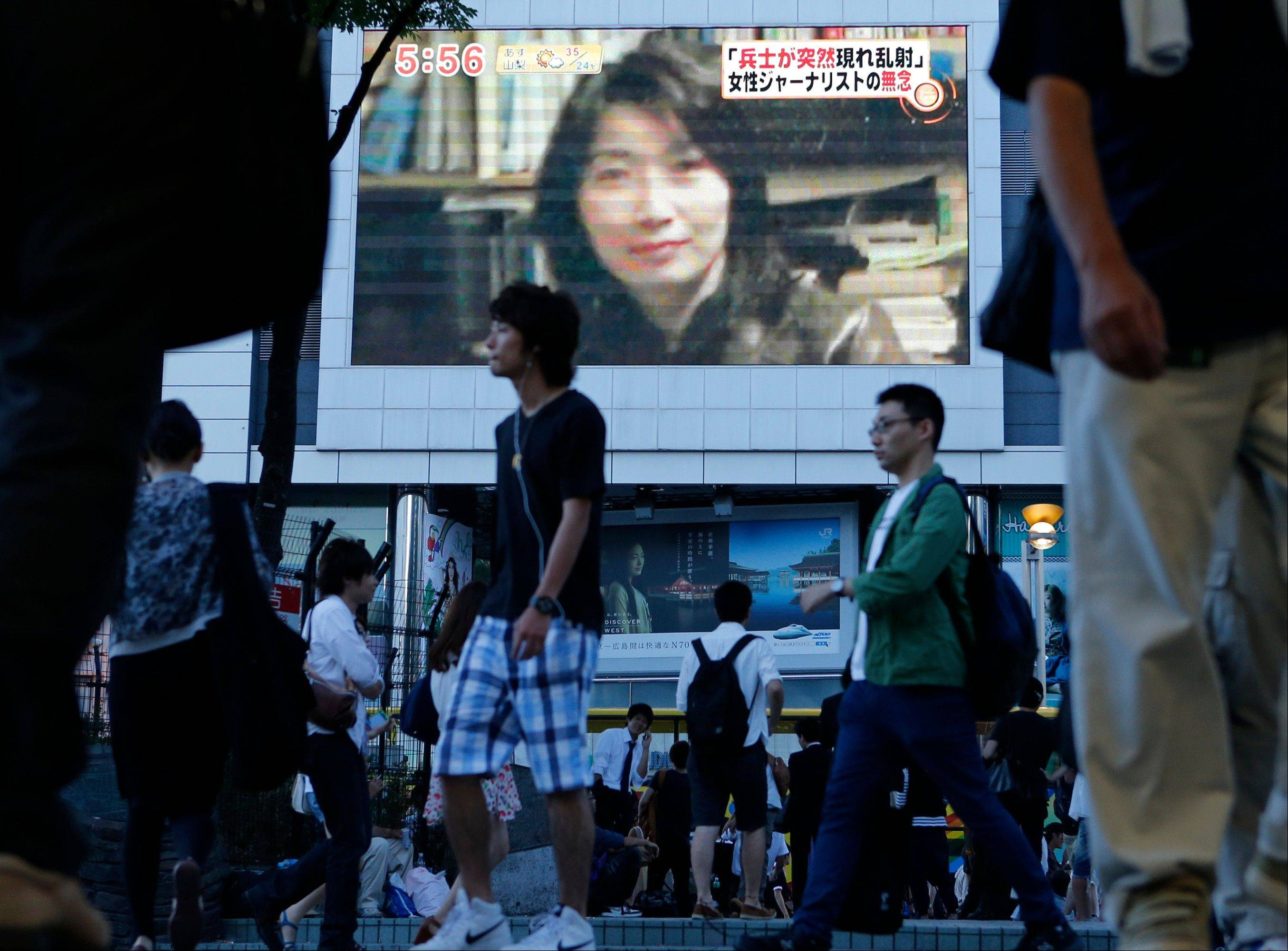 An image of Japanese journalist Mika Yamamoto is shown on a large monitor screen in Tokyo Tuesday, Aug. 21, 2012 during a TV news broadcast reporting her death in Syria. Yamamoto, a veteran war correspondent with The Japan Press, an independent TV news provider that specializes in conflict zone coverage, was killed Monday in the northwestern city of Aleppo, said Masaru Sato, a spokesman with the Foreign Ministry in Tokyo.