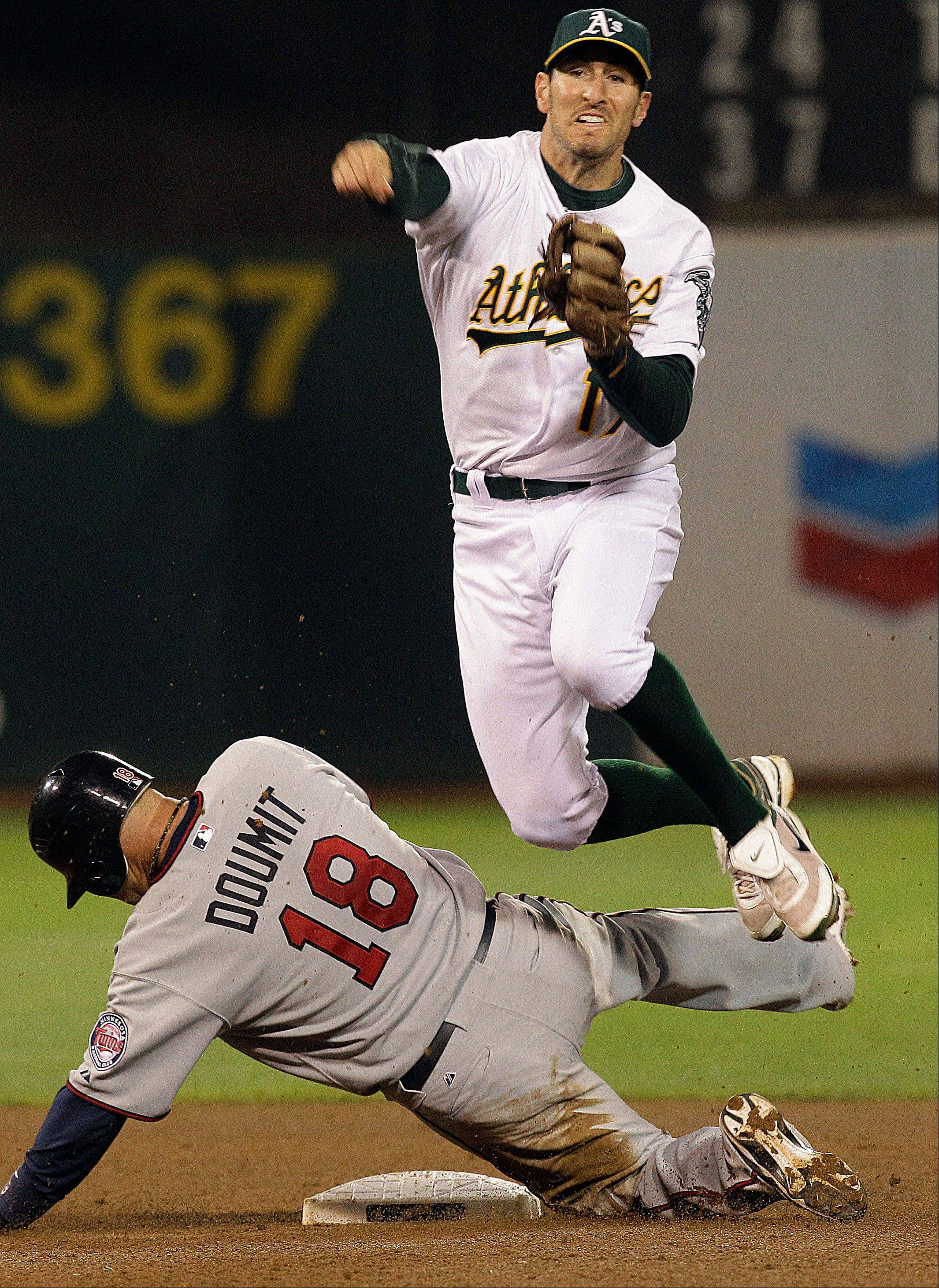 A's second baseman Adam Rosales throws to first over the Twins' Ryan Doumit, completing a triple play hit into by Trevor Plouffe in the fifth inning Tuesday in Oakland, Calif.