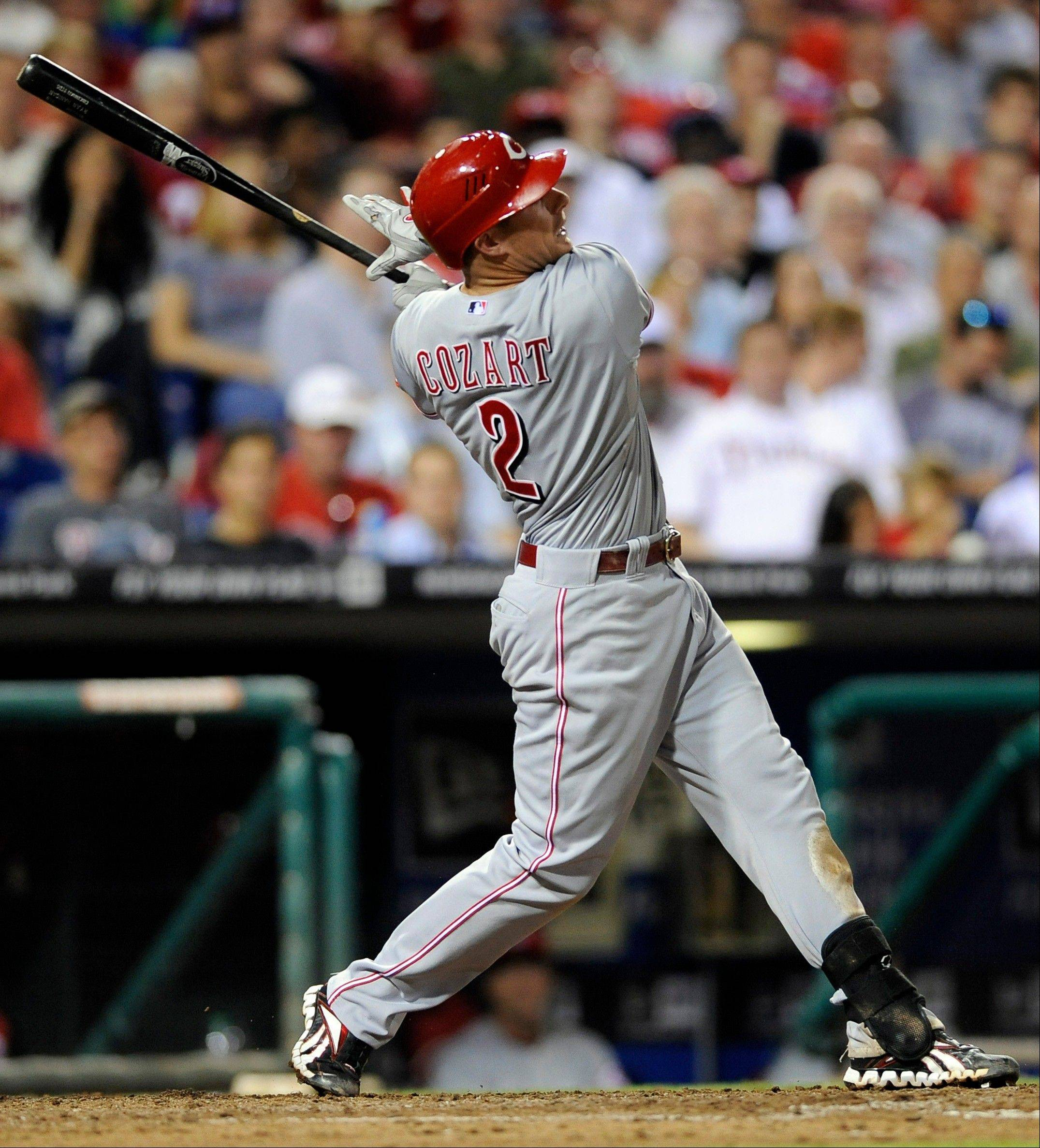The Reds' Zack Cozart swings on a sacrifice fly that scored a run in the seventh inning Tuesday against the Philadelphia Phillies on Tuesday. In the ninth, he hit a go-ahead home run.