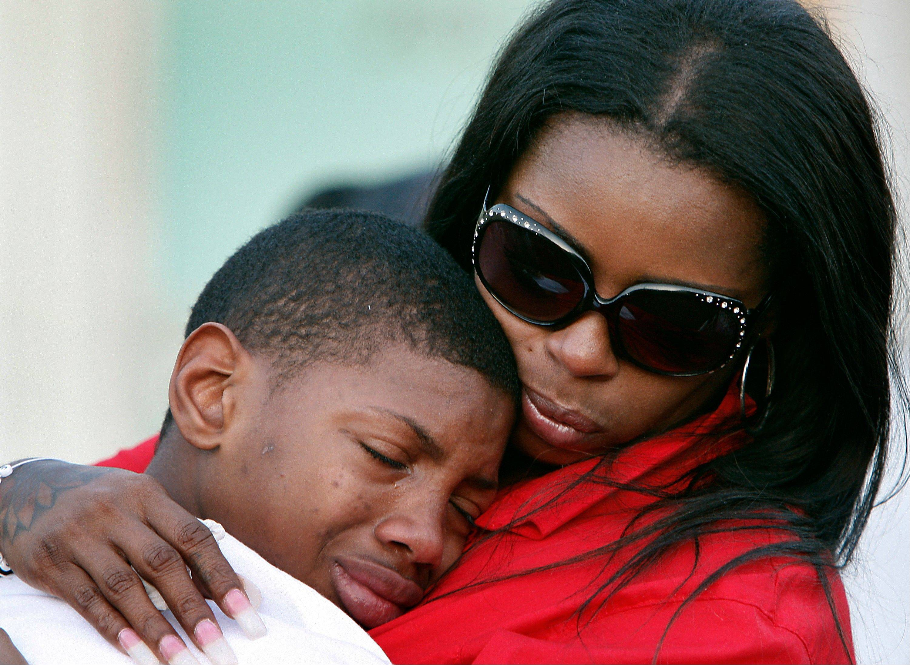 Teresa Carter, right, mother of Chavis Carter, comforts her other son Kizziah Carter on Monday, Aug. 20, 2012 following a prayer vigil held on the grounds of The National Civil Rights Museum in Memphis, Tenn., for Chavis Carter, who Jonesboro, Arkansas, police say committed suicide while handcuffed.