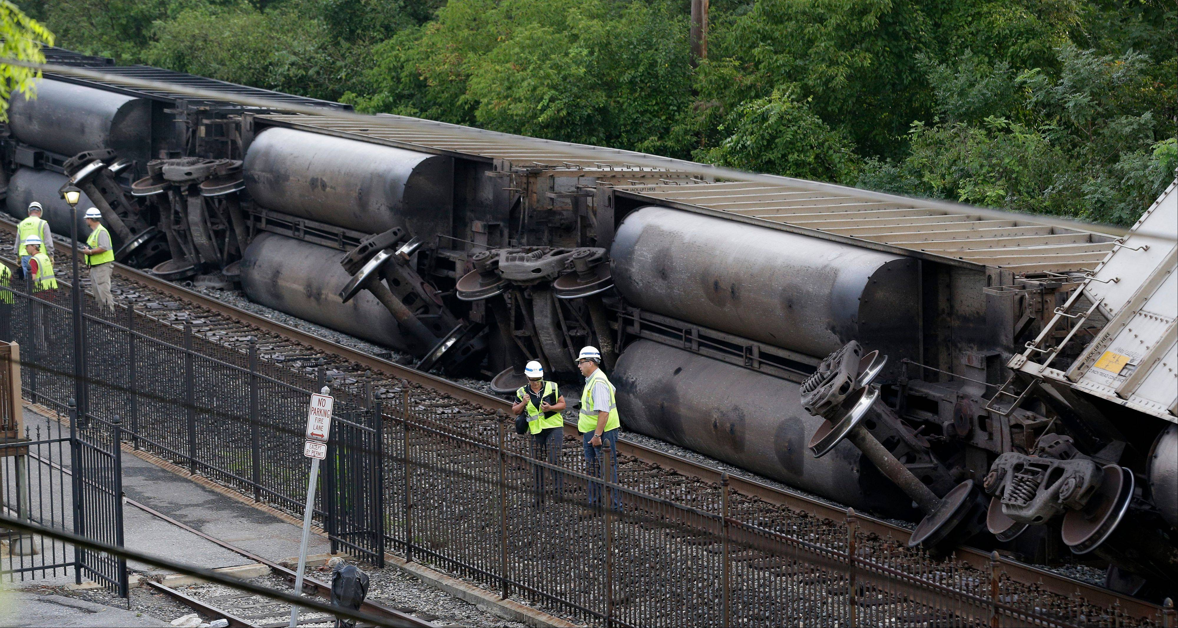 Officials stand near part of a CSX freight train that derailed overnight in Ellicott City, Md., Tuesday, Aug. 21, 2012. Authorities said two people not employed by the railroad were killed in the incident.