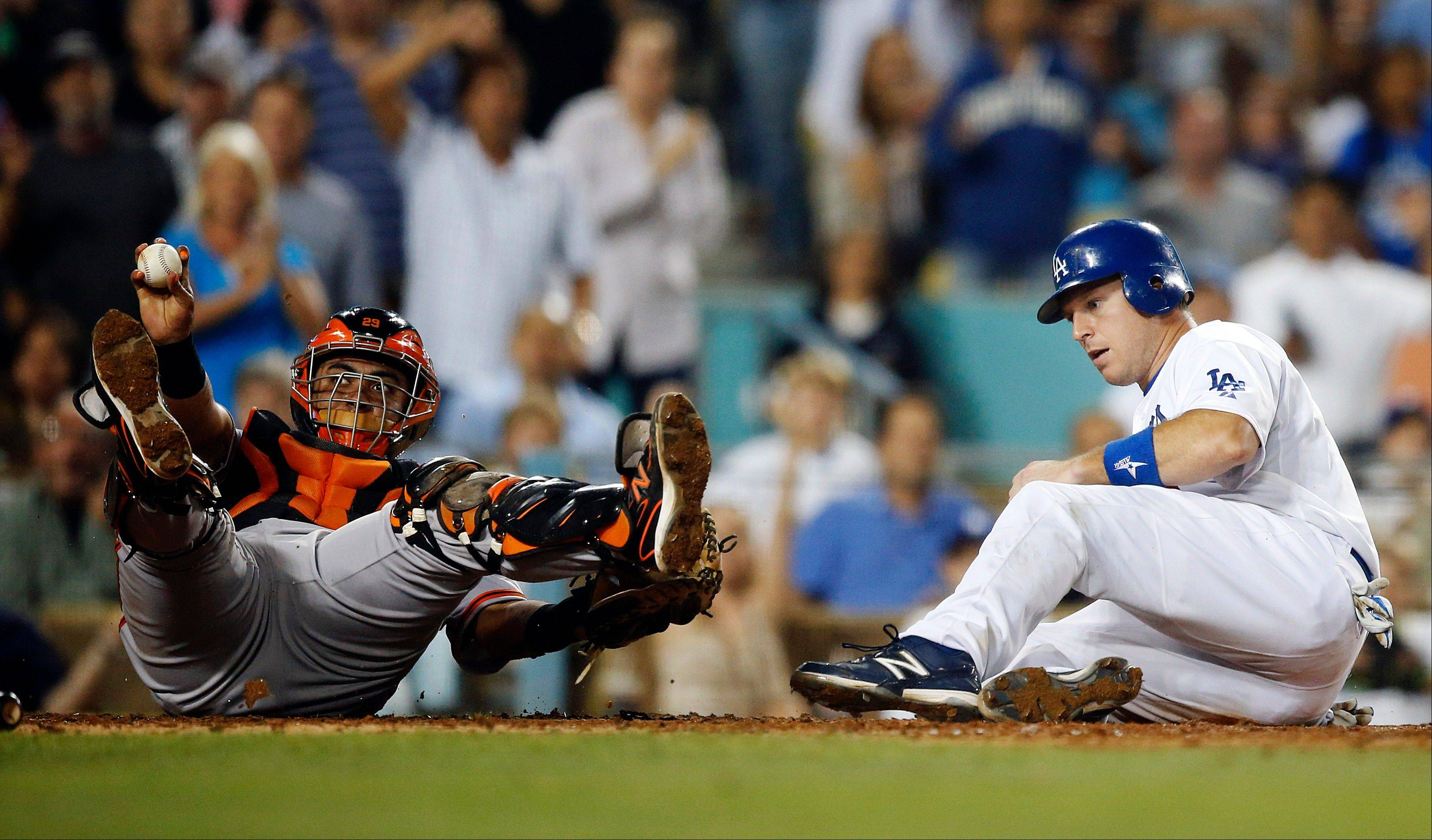 Giants catcher Hector Sanchez holds up the ball after tagging out the Dodgers' A.J. Ellis in the sixth inning Tuesday in Los Angeles.