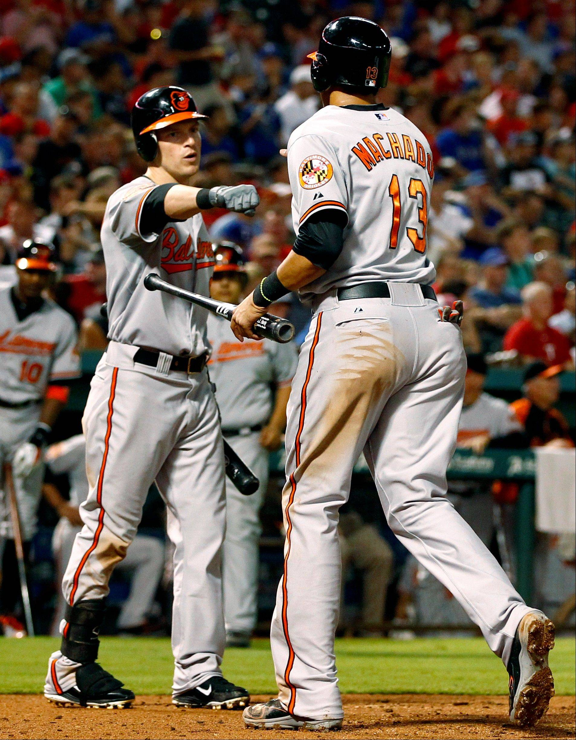 Baltimore's Manny Machado (13) is congratulated by Nate McLouth after scoring a run against the Texas Rangers in the fifth inning Tuesday in Arlington, Texas.