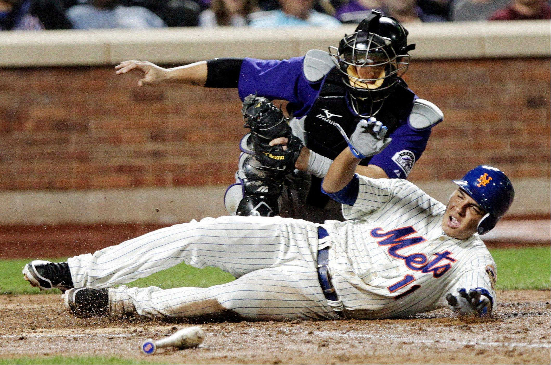 Rockies catcher Ramon Hernandez tags out the Mets' Ruben Tejada at home plate during the sixth inning Tuesday in New York.