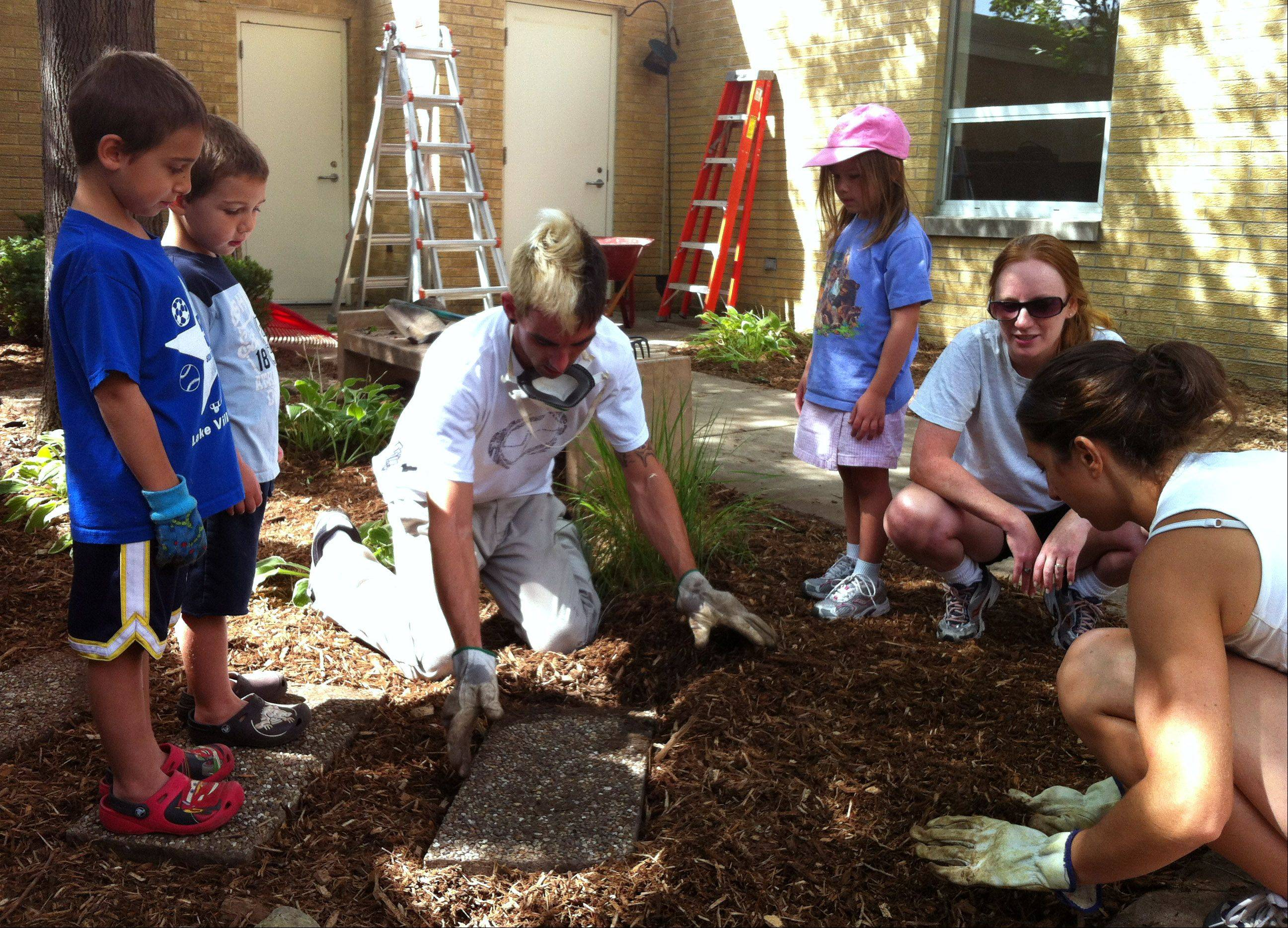 Volunteers work to give the courtyard at Fairhaven School in Mundelein a makeover.