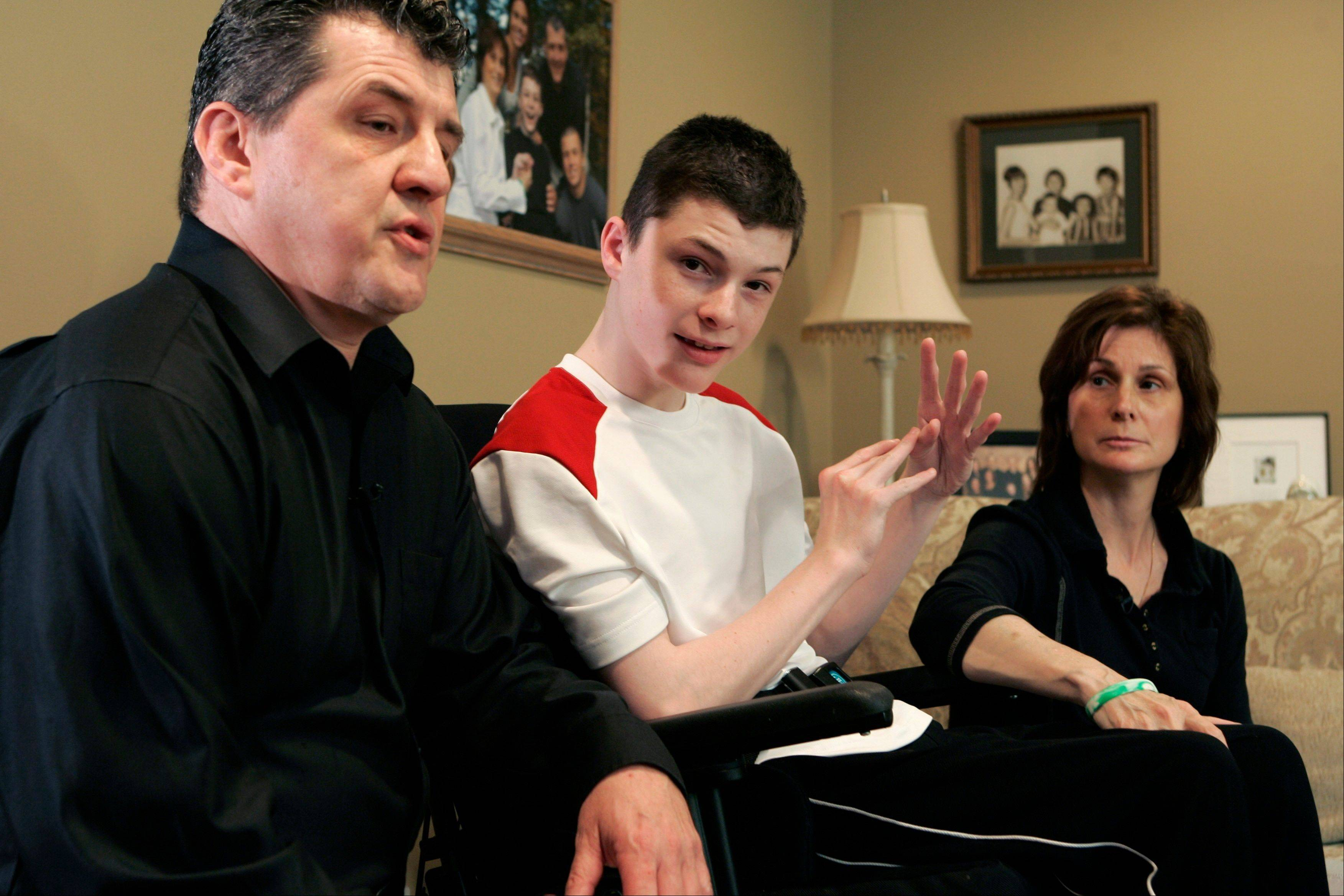 In this file photo from 2008, Steven Domalewski, center, sits with his parents, Joseph and Nancy Domalewski, during an interview at their home in Wayne, N.J. Domalewski was left brain-damaged after being struck by a line drive while he was playing in a youth baseball game.