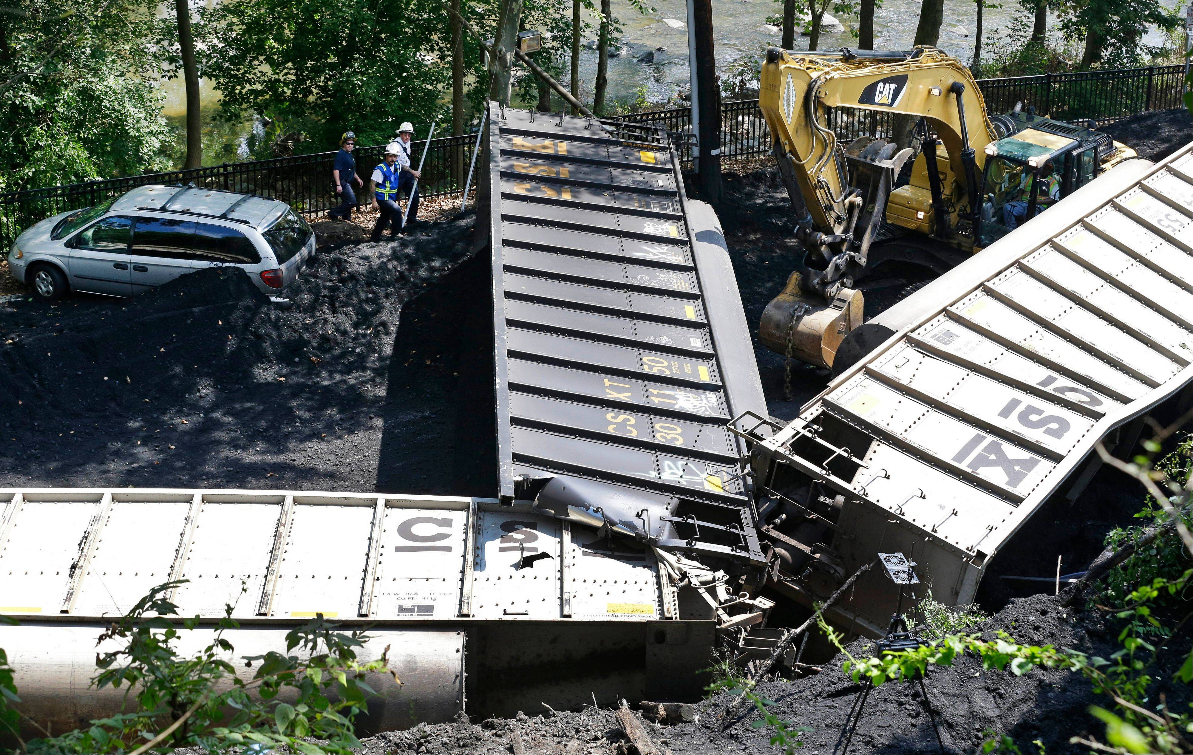 Investigators were checking videos, track conditions and maintenance records Wednesday to find the cause of a deadly train derailment in Maryland and figure out if two young women sitting on a railroad bridge over the town's main street contributed to the crash or if their presence was just a tragic coincidence.