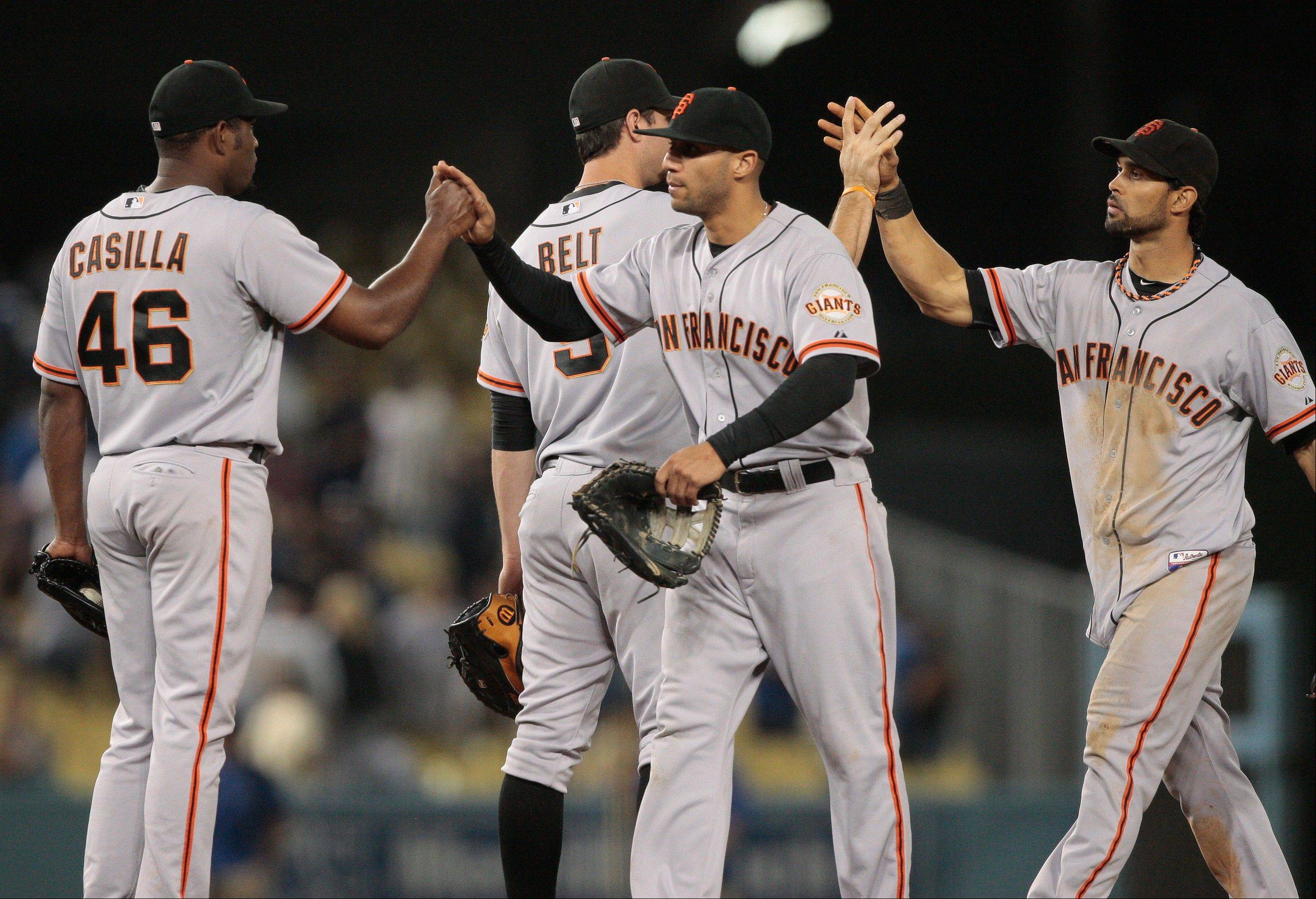 San Francisco closer Santiago Casilla (46) celebrates with teammates after defeating the Dodgers 8-4 on Wednesday in Los Angeles.
