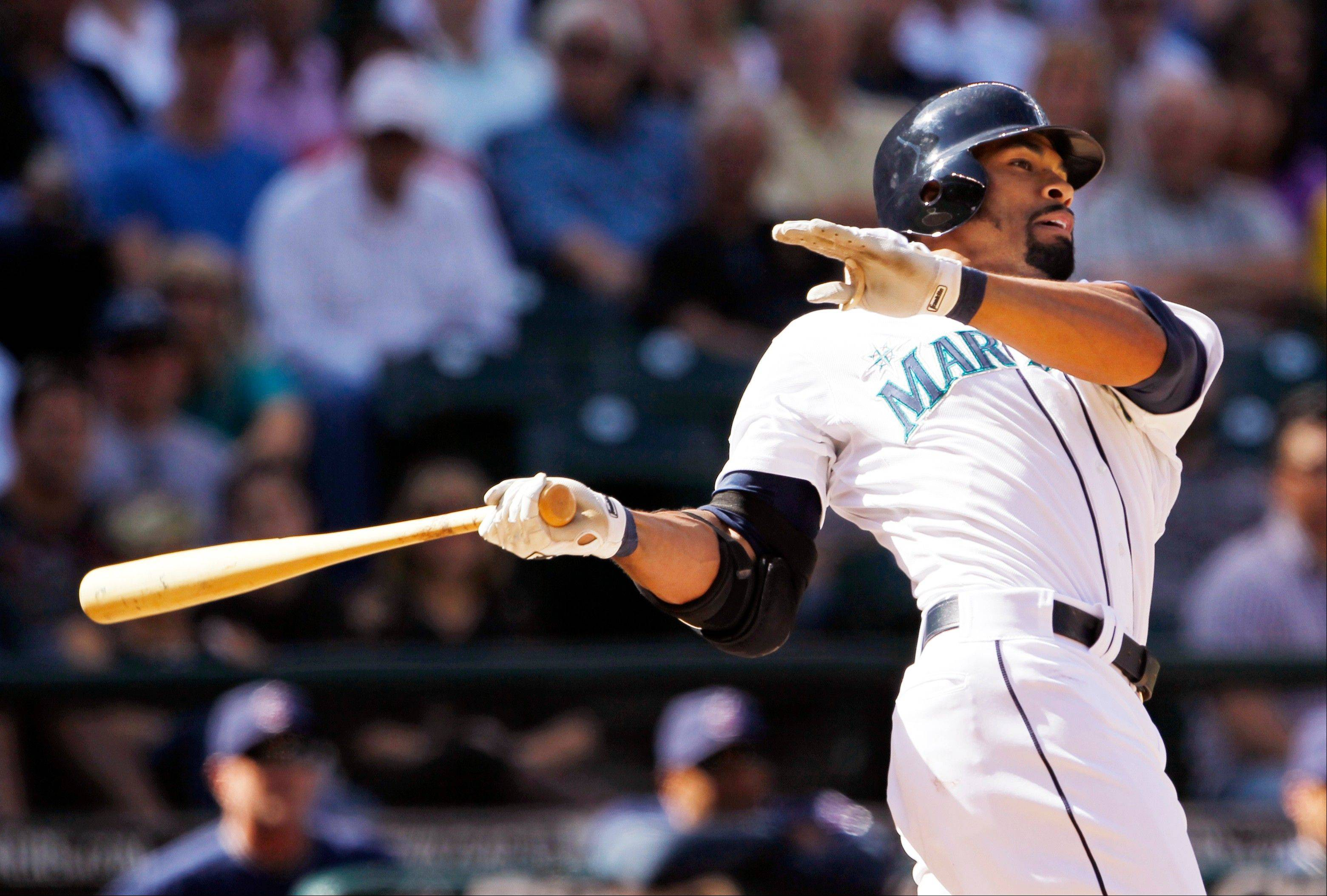 The Mariners' Eric Thames hits a two-run double against the Cleveland Indians in the eighth inning Wednesday in Seattle.