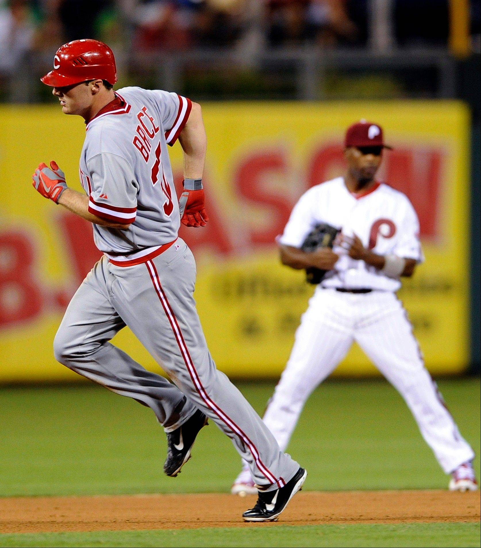 The Reds' Jay Bruce runs past the Phillies' Jimmy Rollins after hitting a home run in the eighth inning Wednesday in Philadelphia.