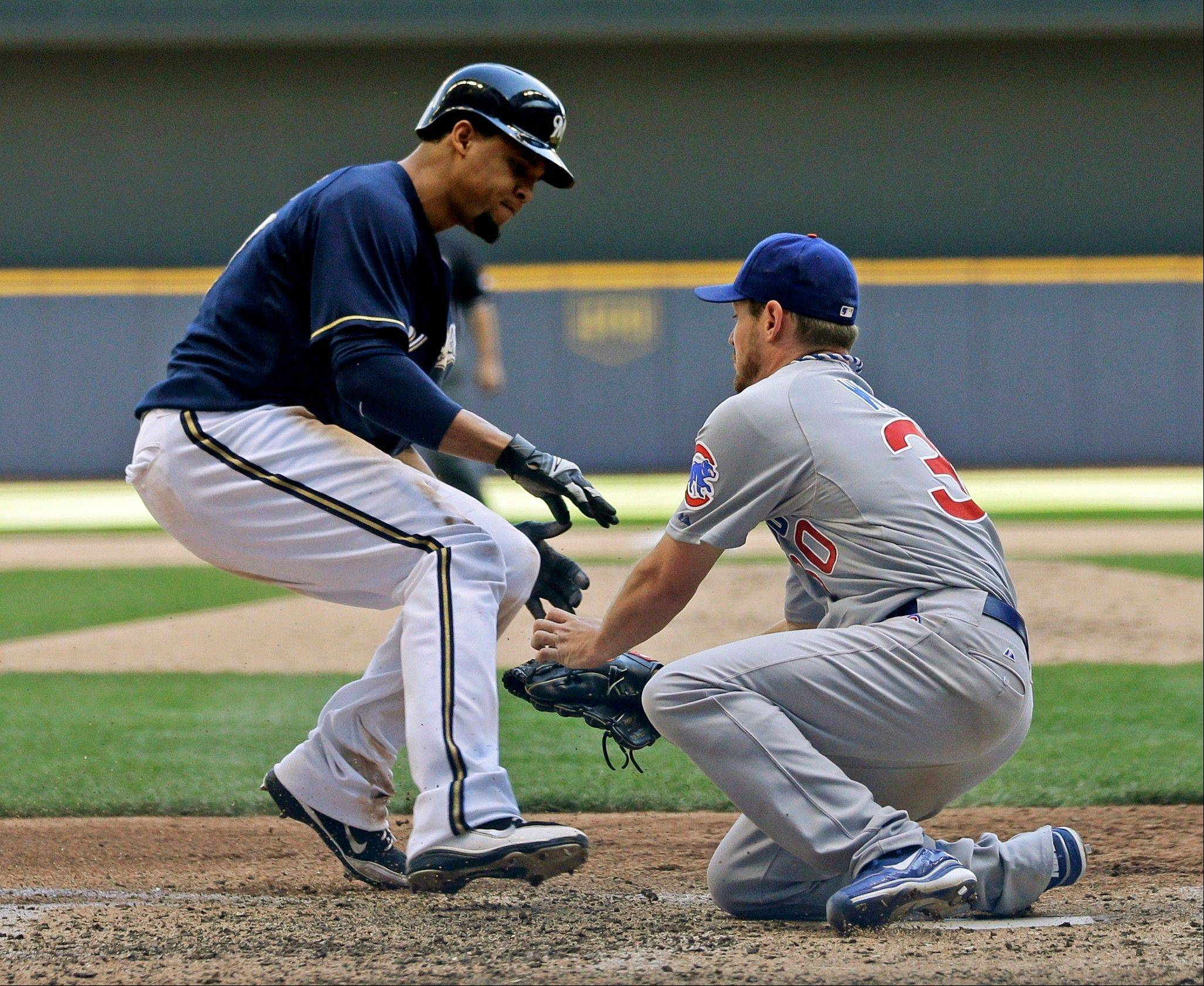 Milwaukee's Carlos Gomez is tagged out by Travis Wood during the seventh inning Wednesday in Milwaukee.