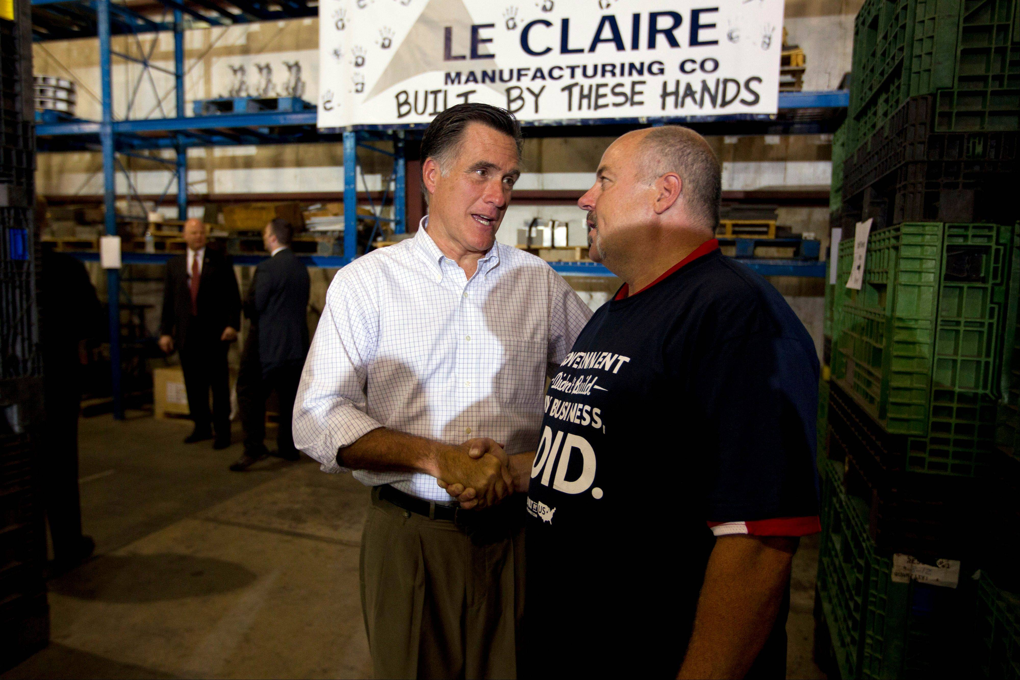 Republican presidential candidate, former Massachusetts Gov. Mitt Romney, left, shakes hands with Ross Murty, the co-owner of the Village Corner Deli, during a campaign stop at LeClaire Manufacturing on Wednesday in Bettendorf, Iowa.