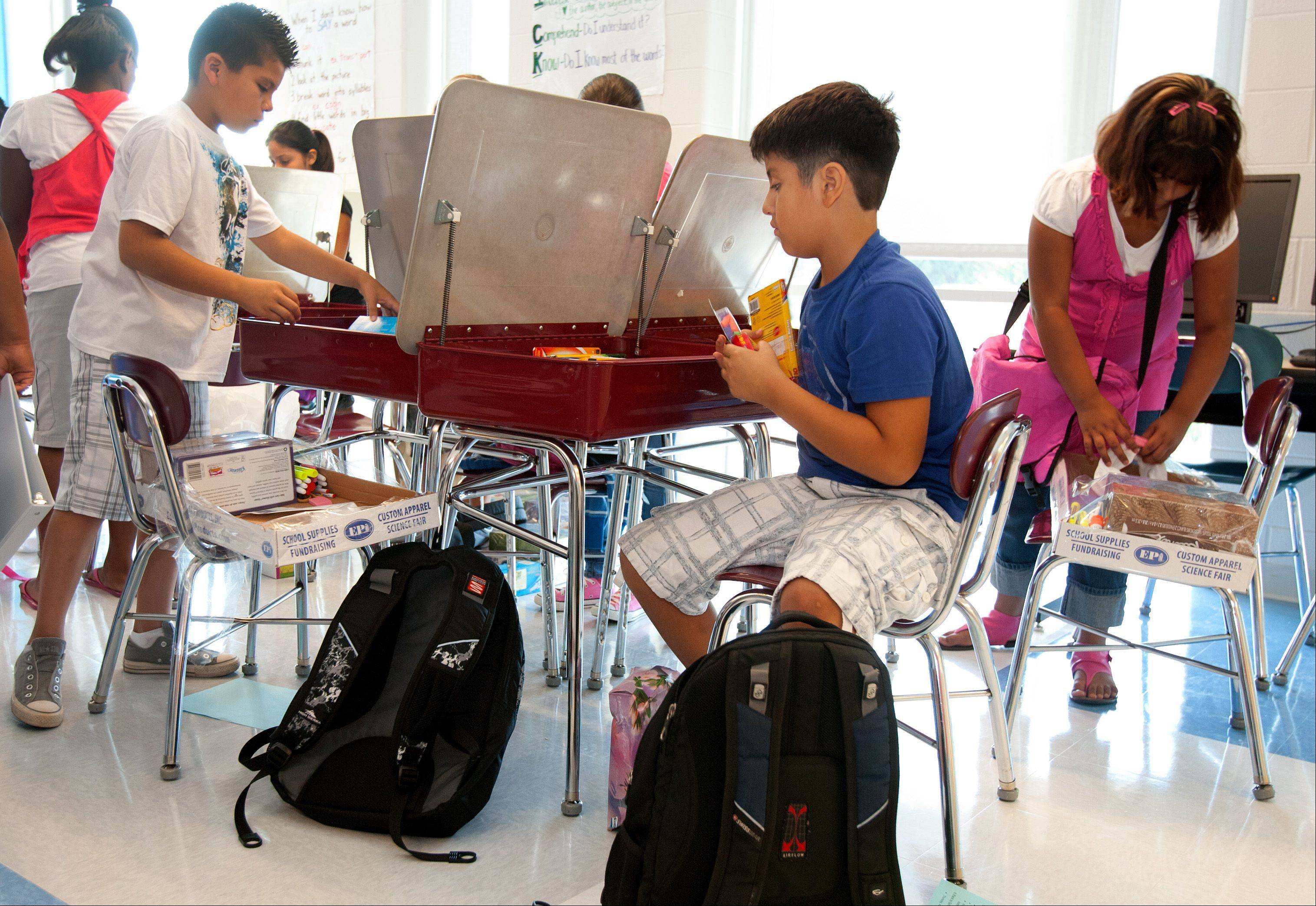 Eric Moreno, seated, puts away school supplies in his new fourth-grade classroom at Tioga School in Bensenville during the first day of classes.