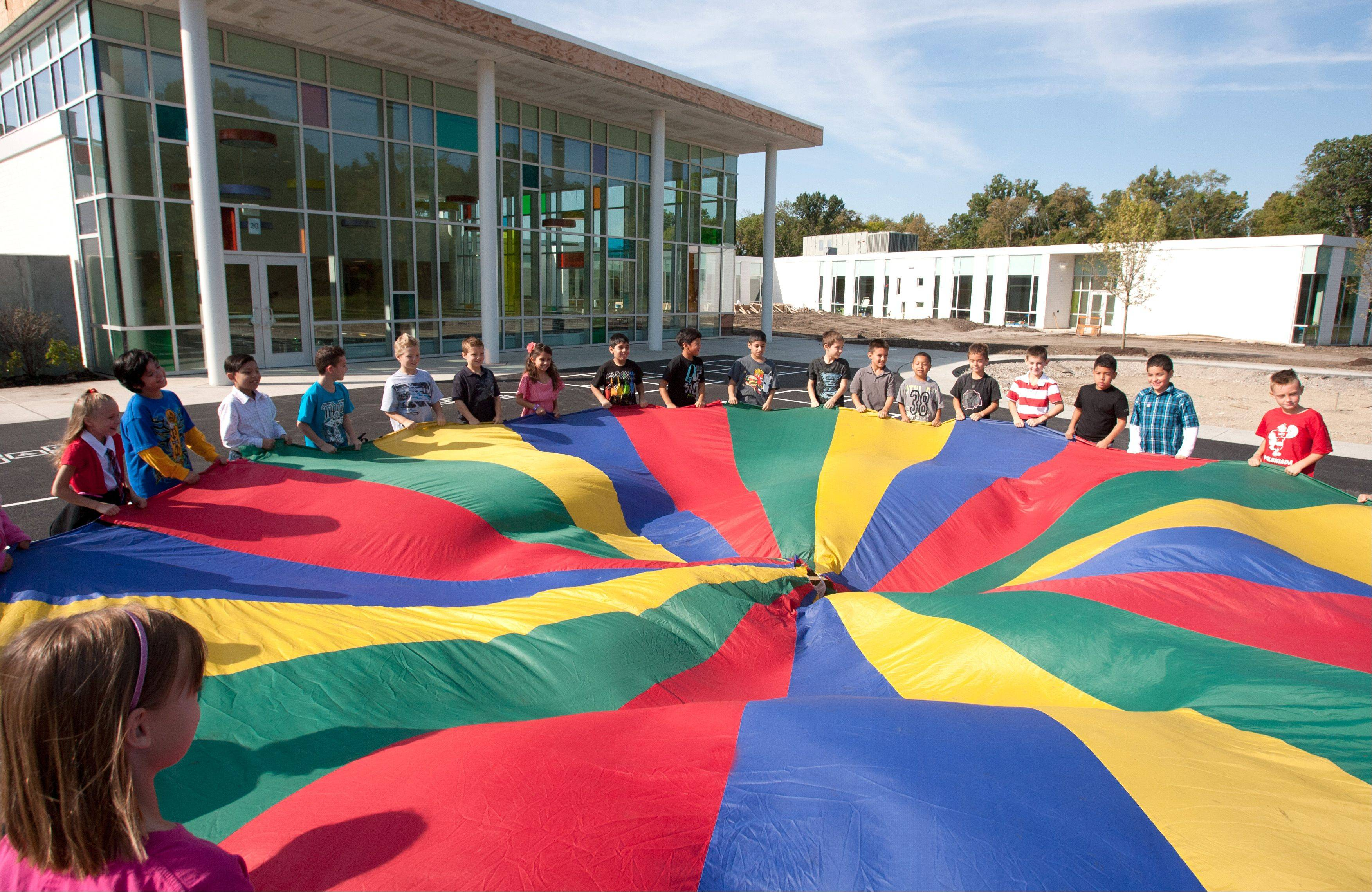 Physical education instructor Brendan Breault's class performs teamwork exercises in front of the newly constructed Johnson School addition during the first day of classes.