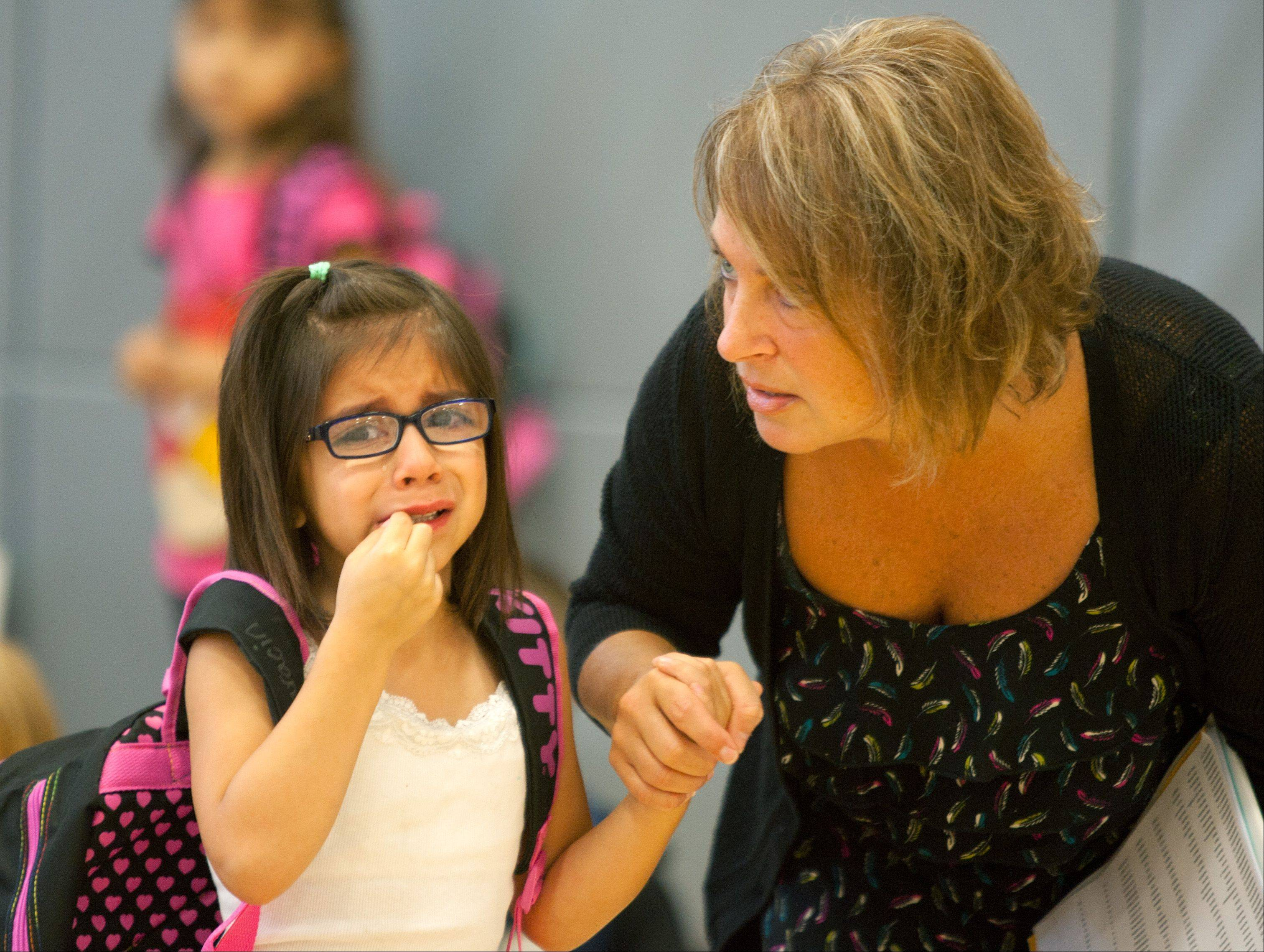 Ava Albaracin is guided through first day jitters by resource teacher Tina Arcivar as Bensenville Elementary District 2 begins merging four of its schools into two.