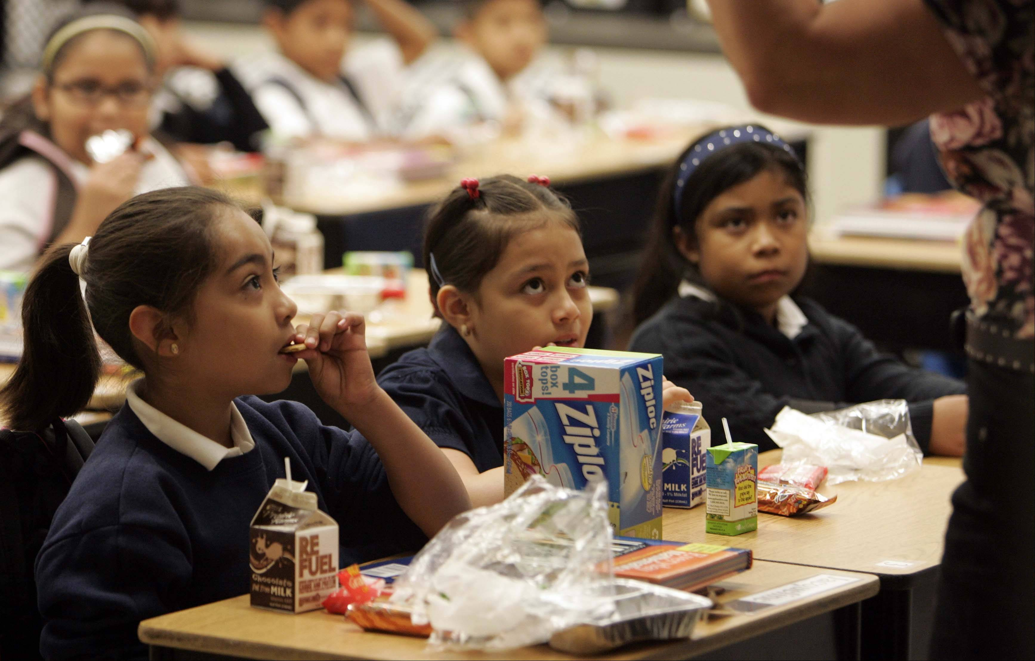 Jacqueline Castillo, left, listens to her teacher Sylvia Eagels Wednesday as she eats her breakfast during the first day of school at Gifford Elementary School in Elgin. Harriet Gifford is one of 10 schools in Elgin Area School District U-46 that now offer a free breakfast to each child every day.