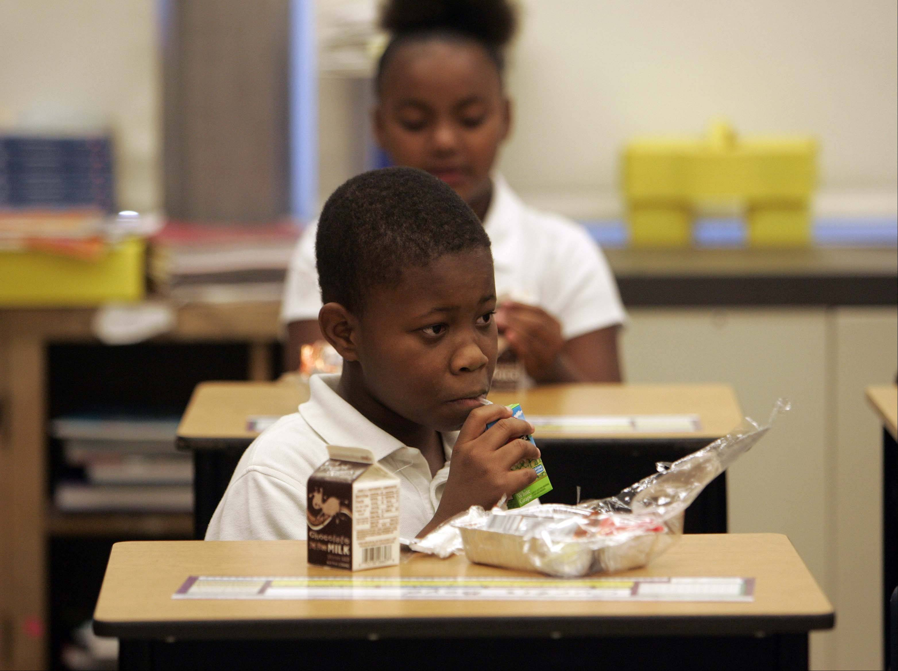 Curtis Byod in Michael Preston's fifth-grade class finishes his breakfast Wednesday during the first day of school at Gifford Elementary School in Elgin. Harriet Gifford is one of 10 schools in Elgin Area School District U-46 that now offer a free breakfast to each child every day.