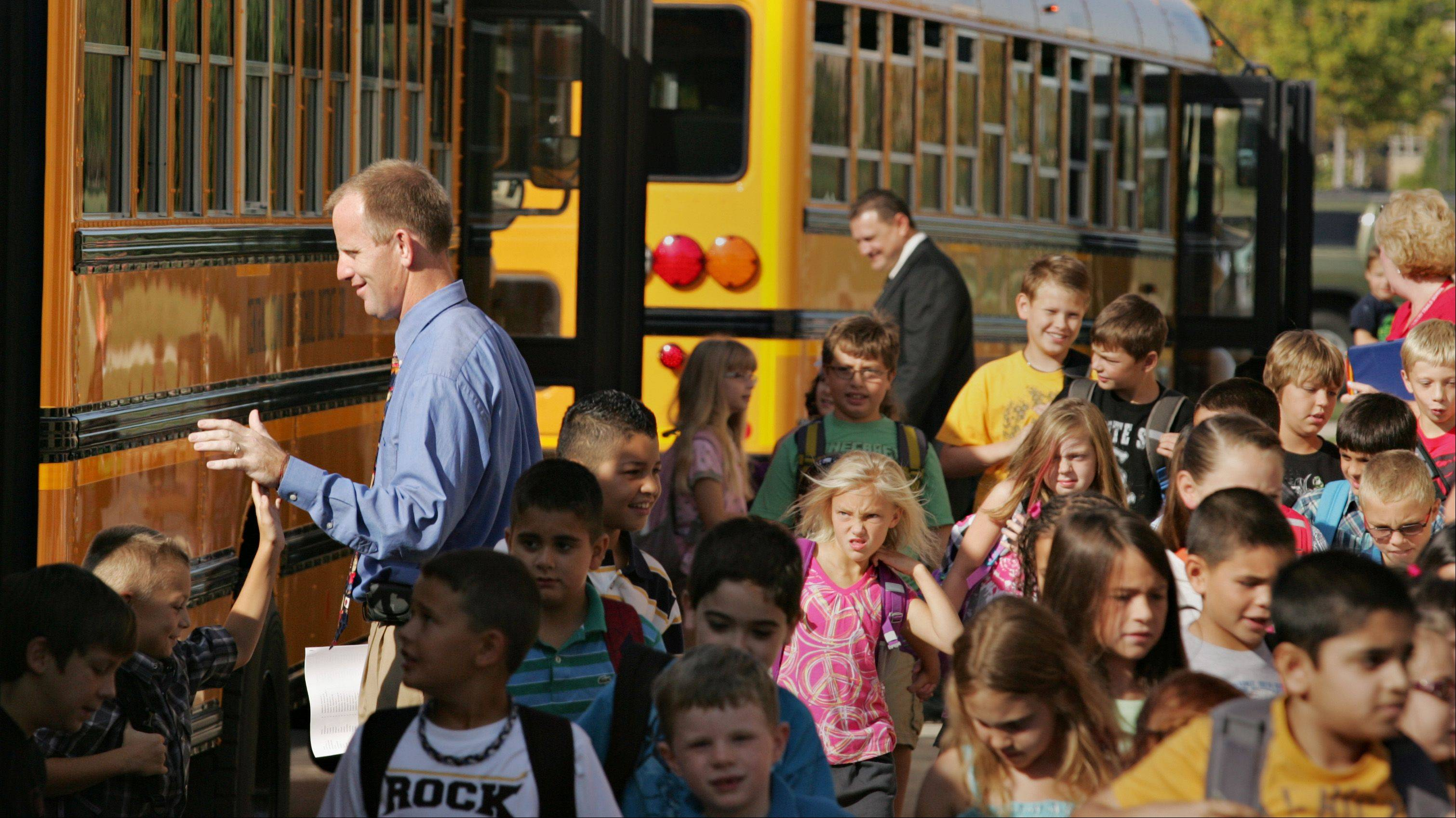New Country Trails Elementary School principal Jeff King high fives students as they arrive by bus on the first day of school in District 301 on Elgin's far-west side.
