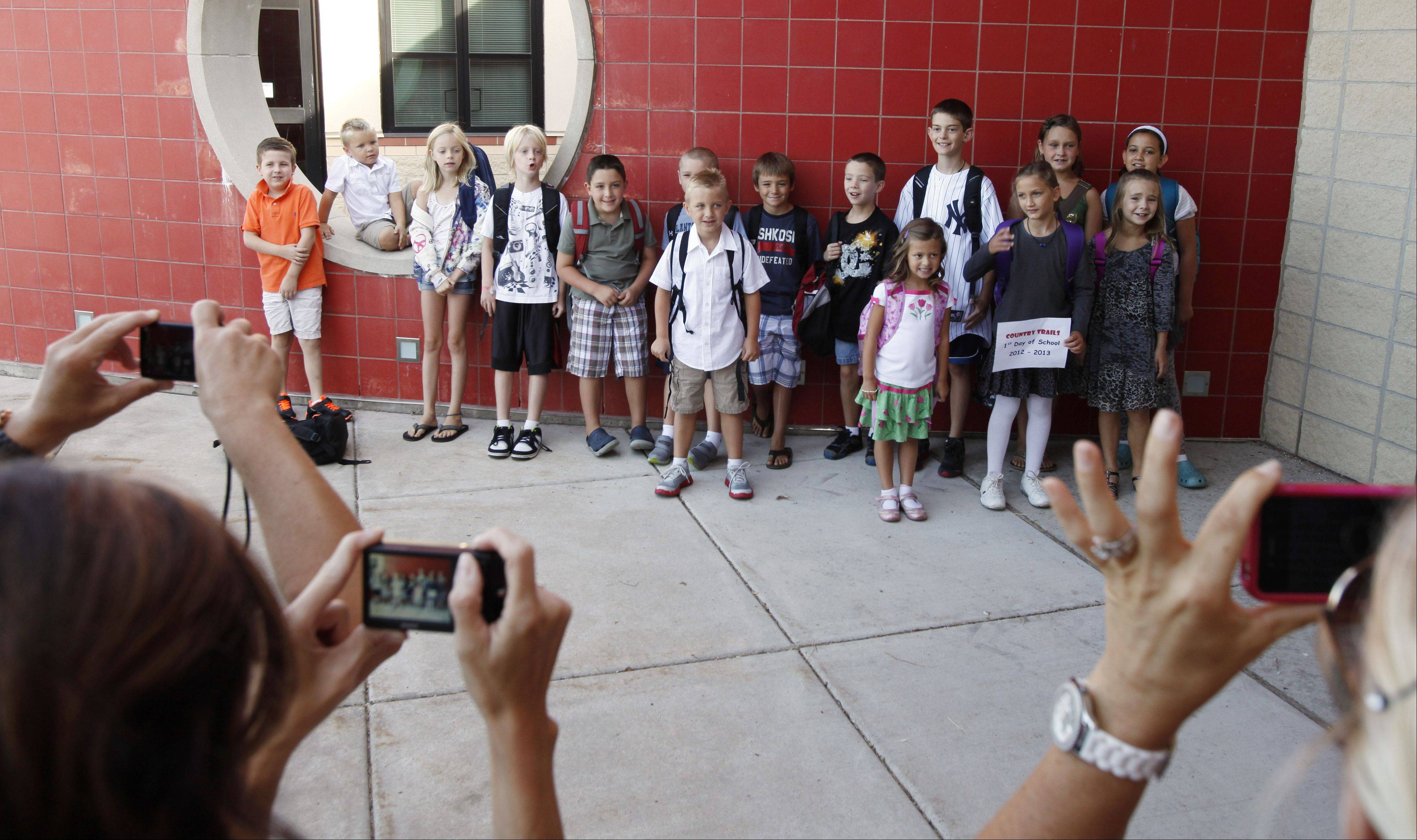 A group of moms take photos of their children before they head inside for the first day of school at Country Trails Elementary School on Elgin's far-west side. School District 301 started classes Wednesday along with many other regional school districts.