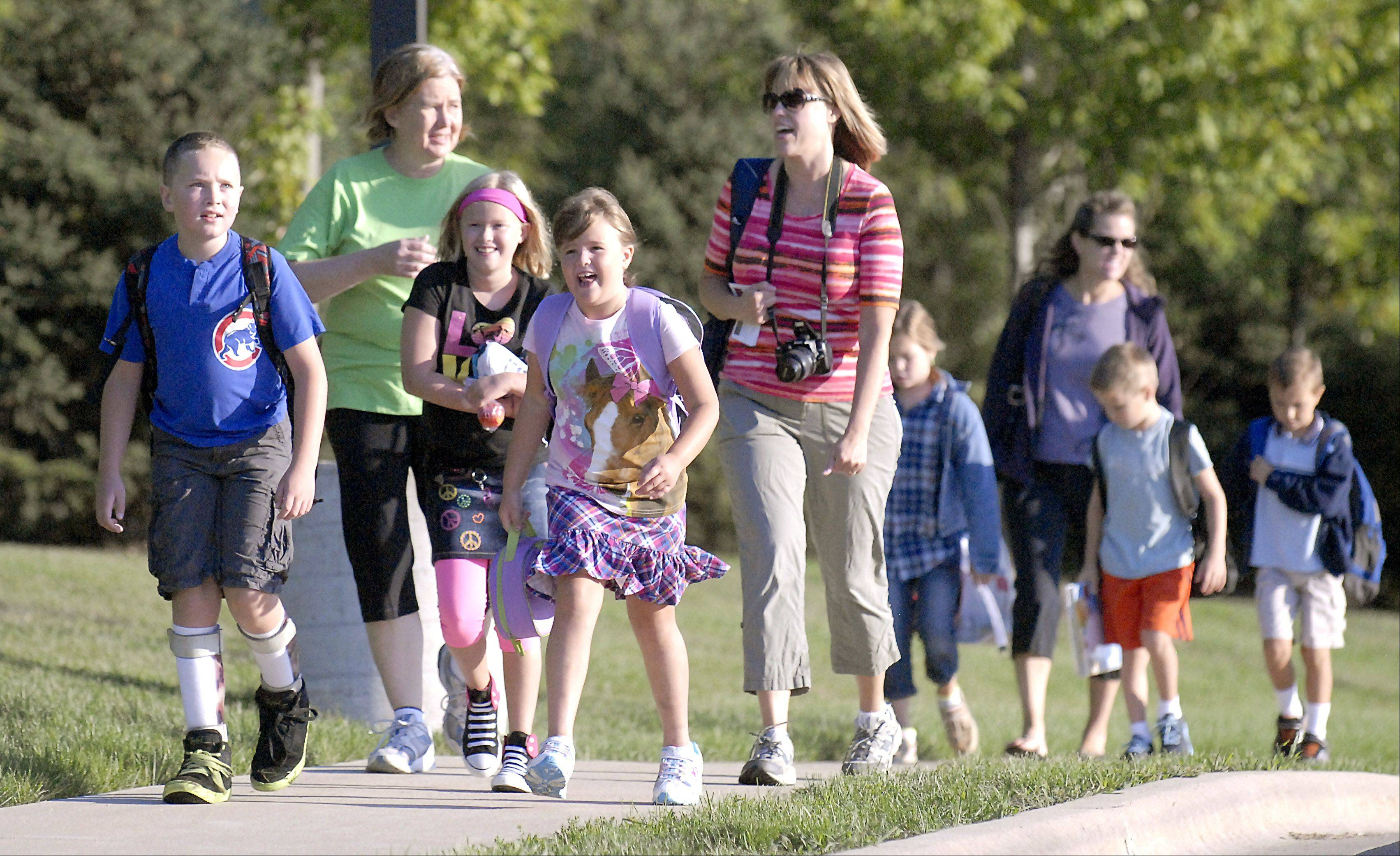 Liam Jackowiec, 10, with Amy Ralston, 8, and her sister Dana, 6, walk with their mothers Marg Jackowiec and Cathy Ralston to Williamsburg Elementary School for the first day of school in Geneva on Wednesday.
