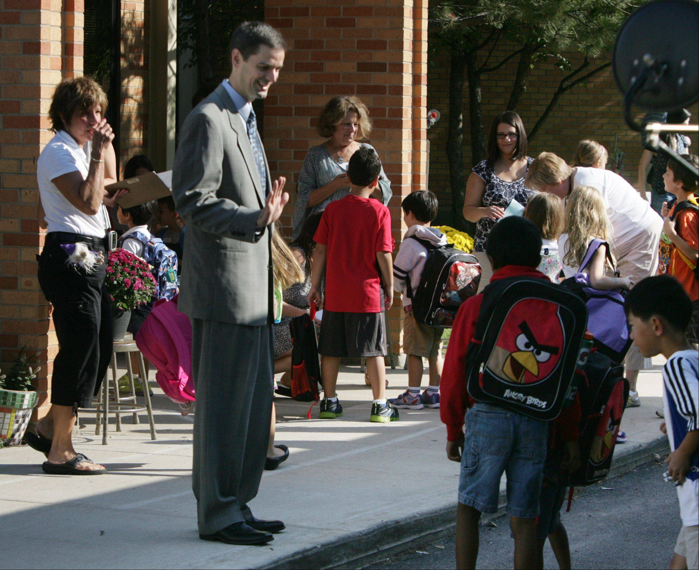 New superintendent Scott Warren greets children walking off the bus during the first day at Laura B. Sprague School in Lincolnshire Wednesday. Warren is the superintendent for the Lincolnshire-Prairie View School District 103.