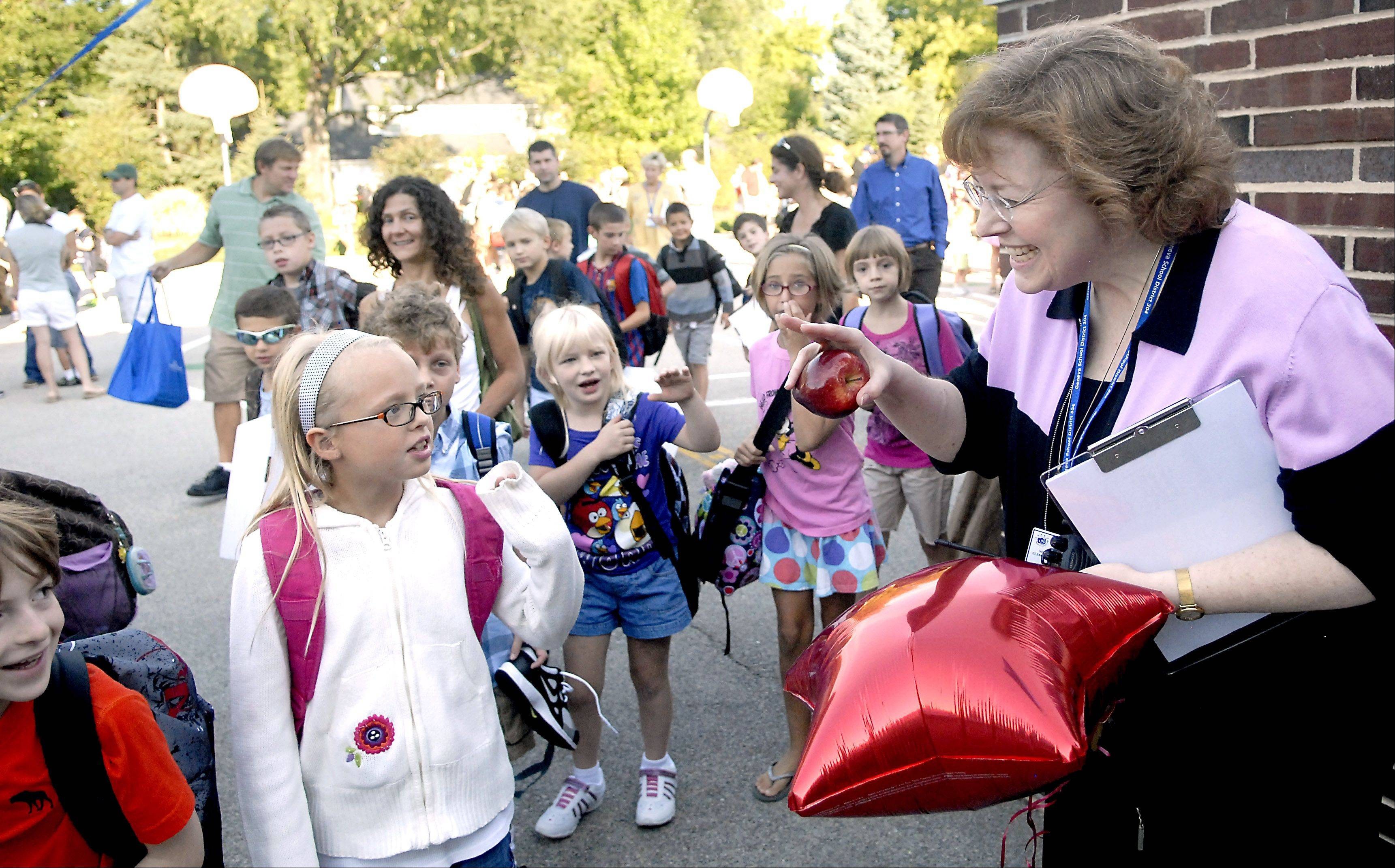 Clutching her first apple of the year, Williamsburg Elementary School principal Julie Dye greets and waves to students as they file into the building for the first day of school in Geneva on Wednesday.