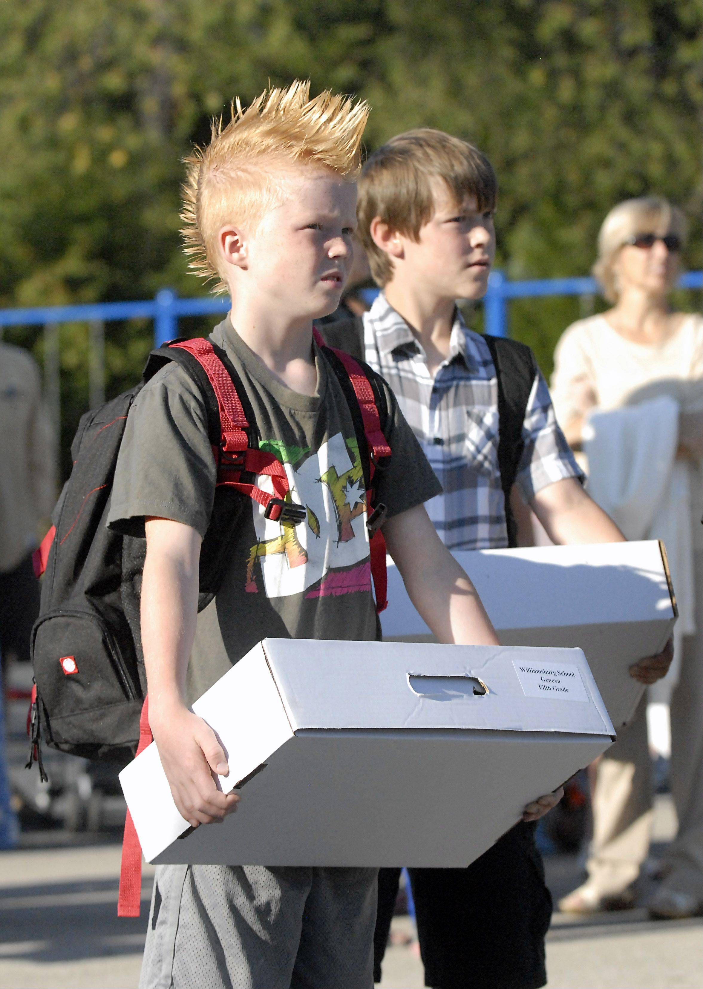 Juda Reynolds, 10, holds his box of school supplies ready to start the fifth grade on the first day of school at Williamsburg Elementary School.
