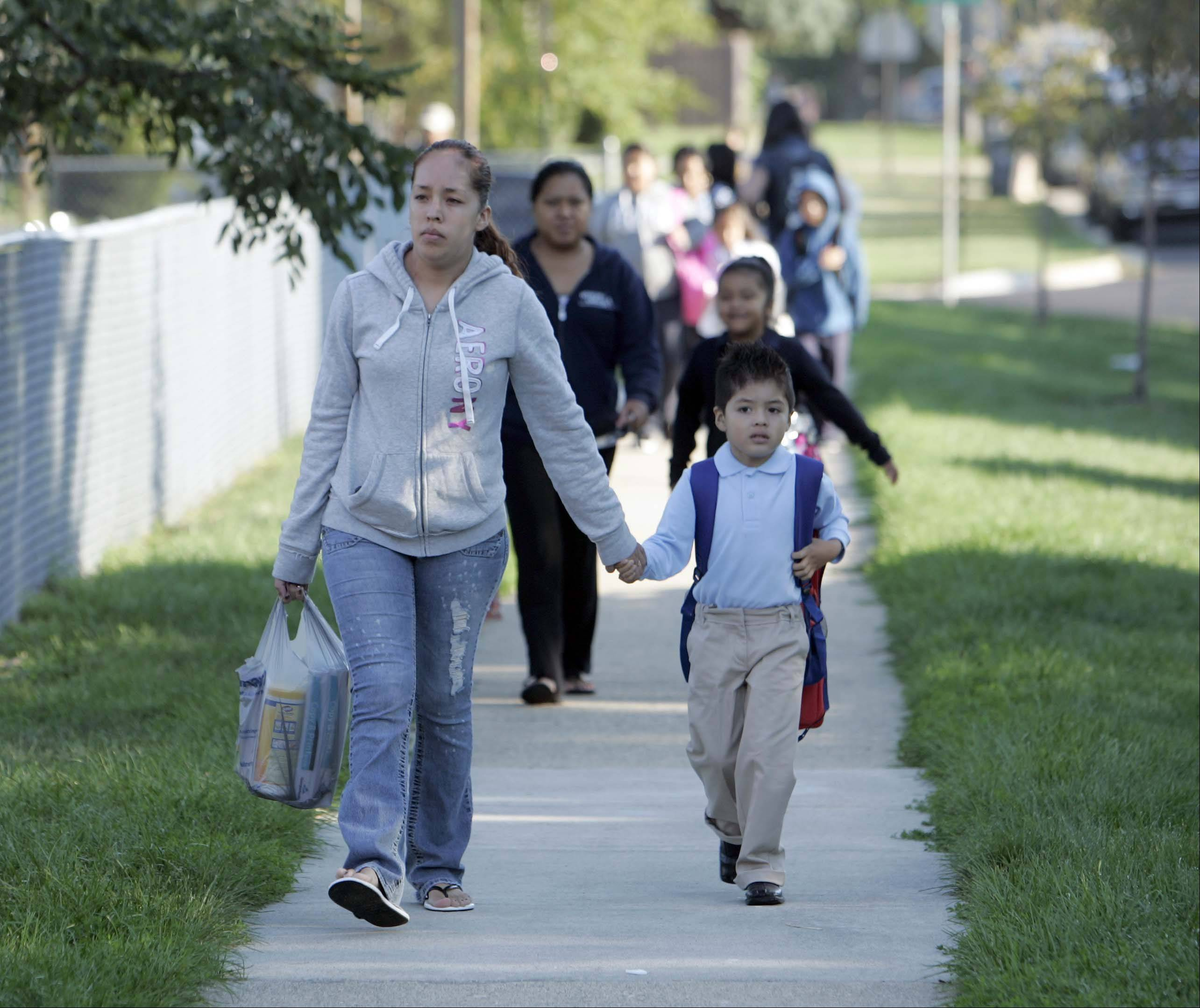 Five-year-old Erick Flores walks hand-in-hand with his mother Monica Urbieta to the first day of school at Gifford Elementary School in Elgin.