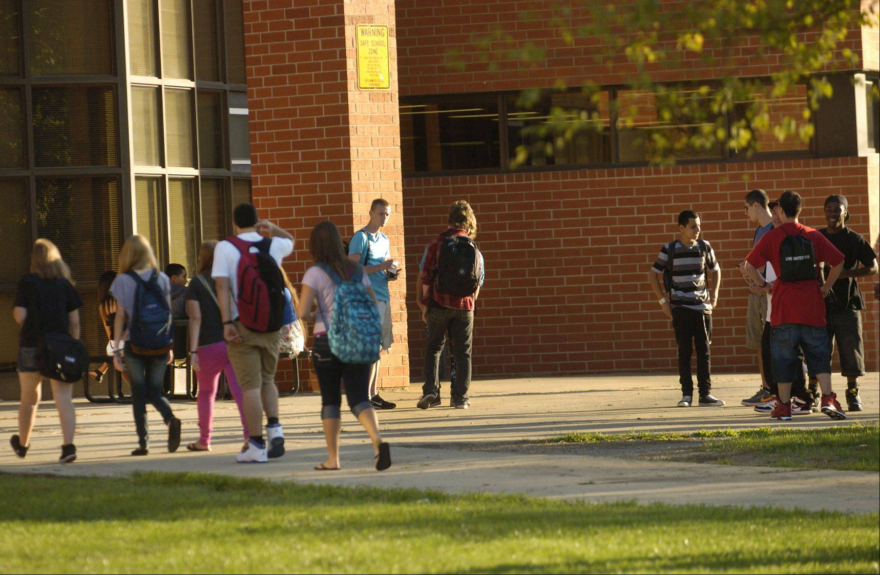 Students make their way through the early morning sunlight to attend the first day of school at Streamwood High School.