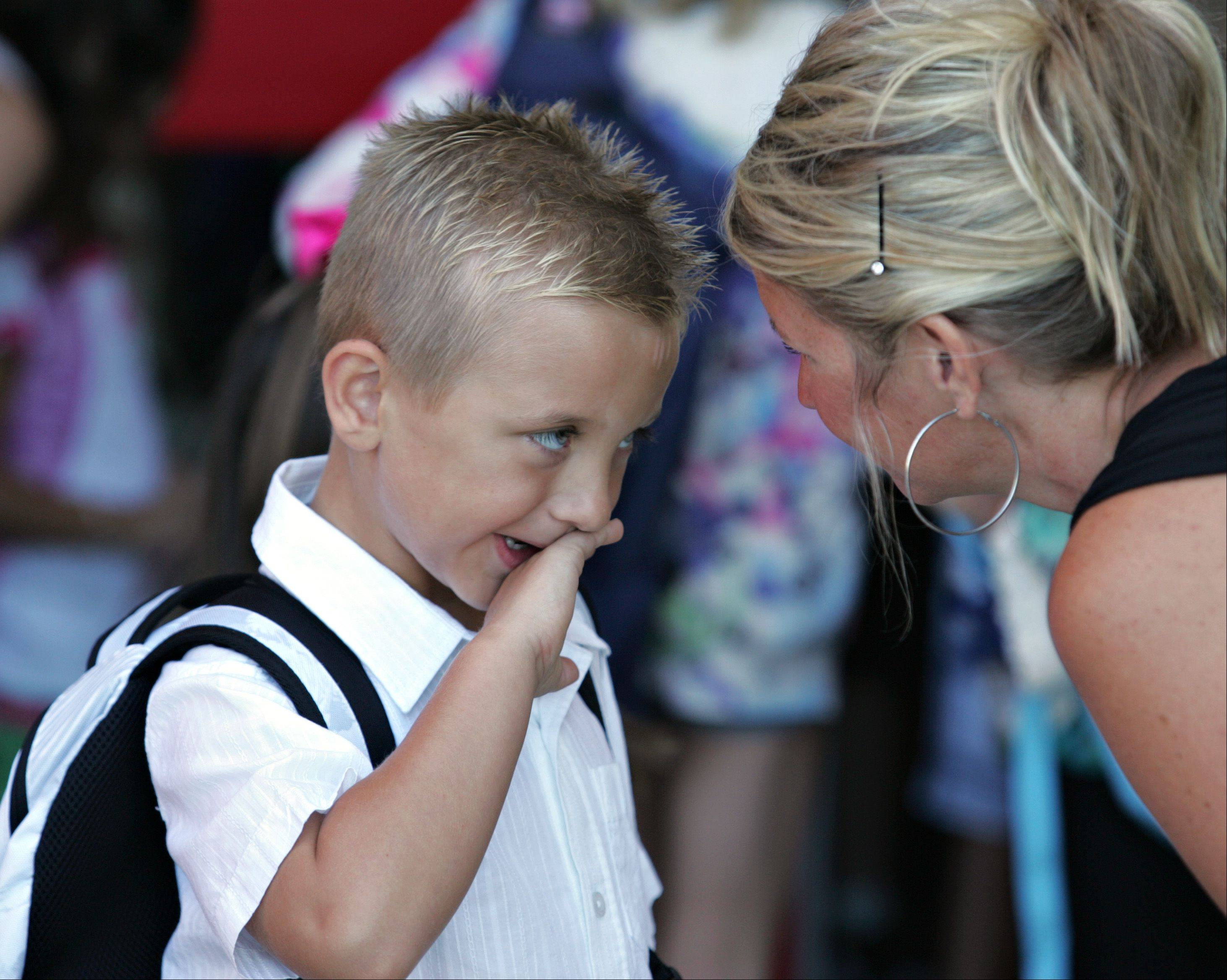 First-grader Mason Rosborough wipes his mouth after his mother Caryn tried to do some last-minute cleanup on him just before the first day of school at Country Trails Elementary School in Elgin.