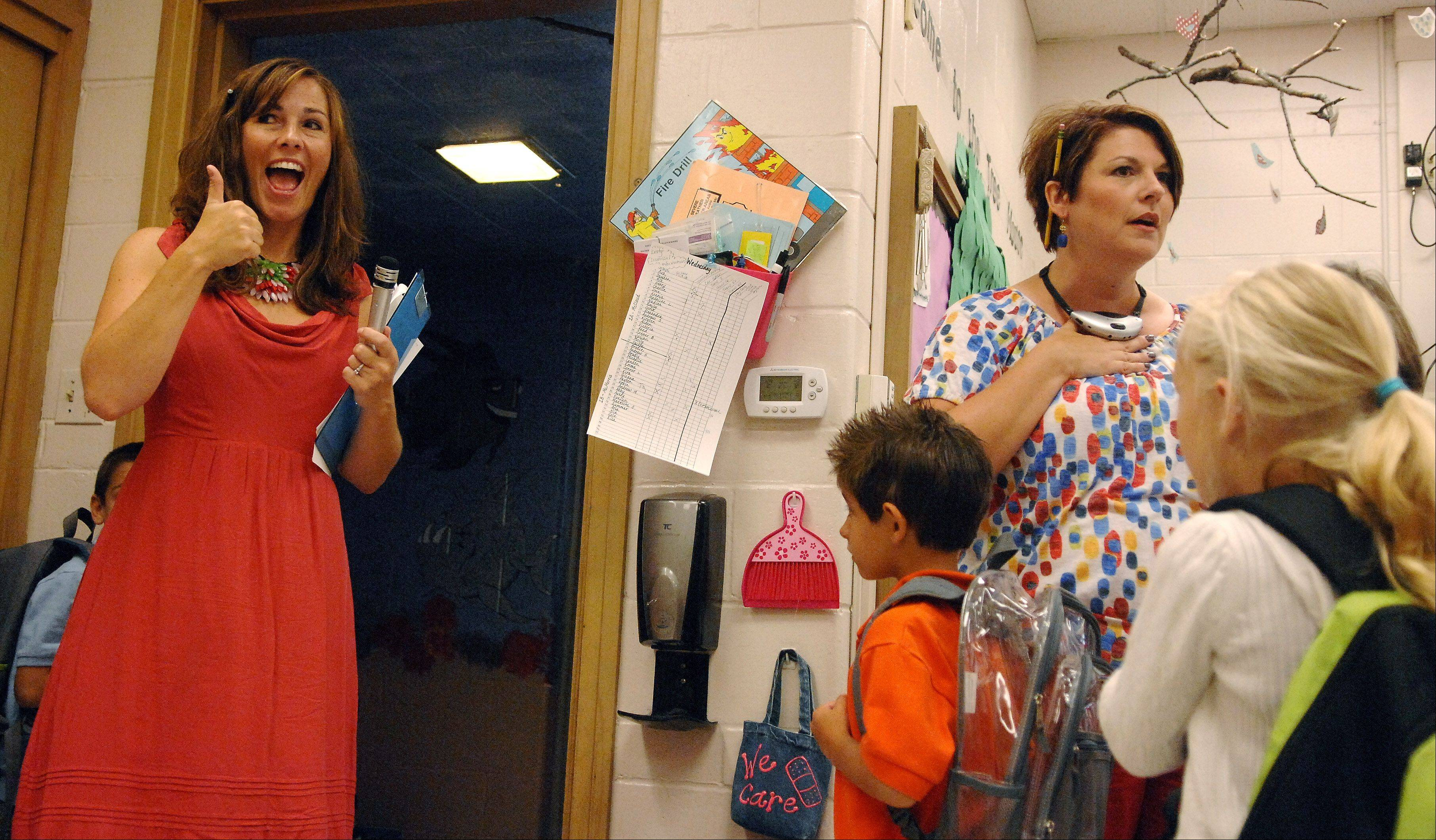 First-grade teacher Marti McCloud gives a thumbs-up to the performance of her students while her co-teacher Lisa McMorris gives them instructions before moving to their other class across the hall during the first day of school at Lincoln Elemetary School in St. Charles Wednesday. McCloud and McMorris are team teaching a class of 44 students. This is the first year for team teaching at Lincoln and they're using it for 2 first-grade classes.