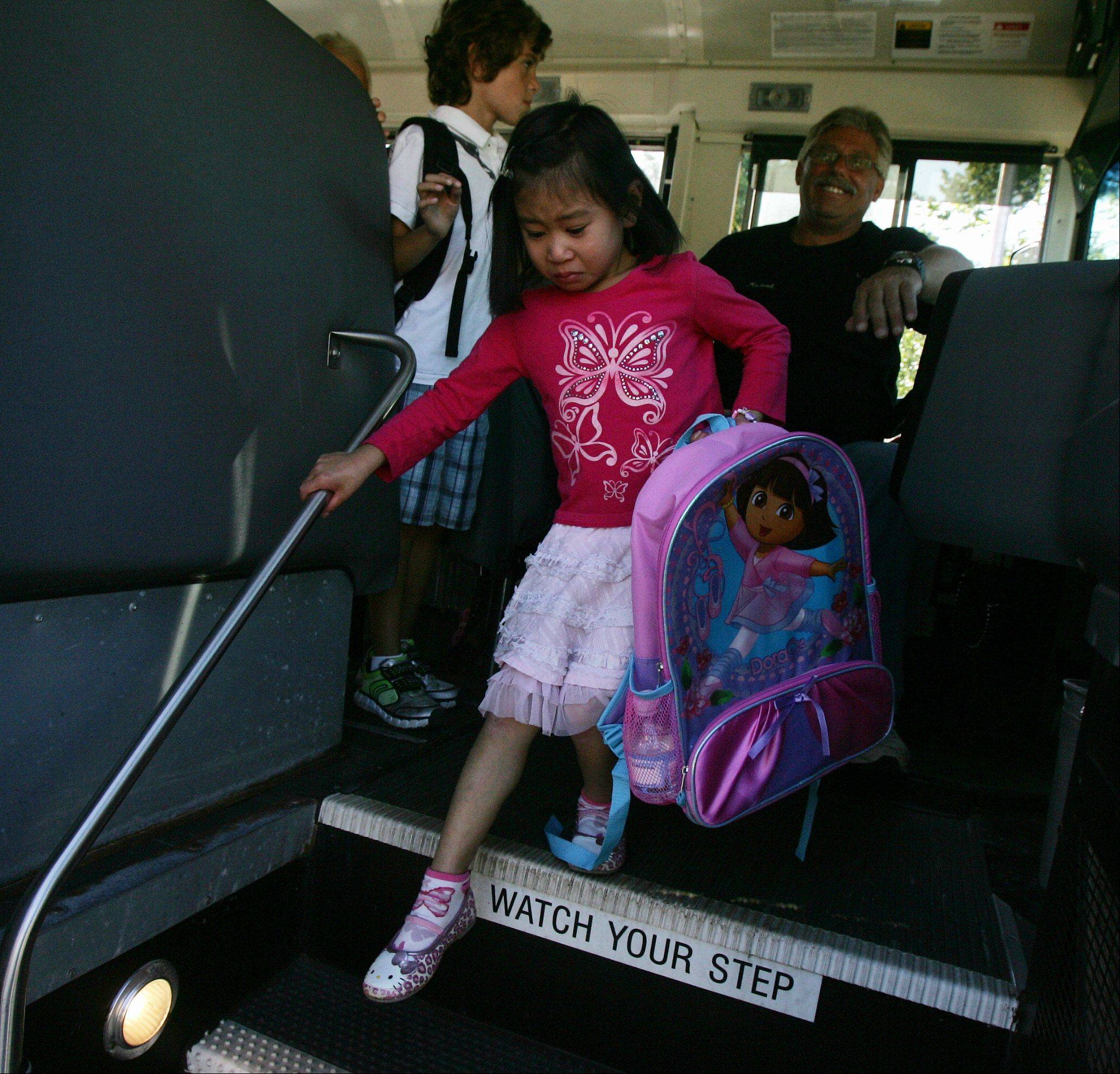 Kindergartner Maggie Kuang walks off the bus during the first day at Laura B. Sprague School in Lincolnshire Wednesday.