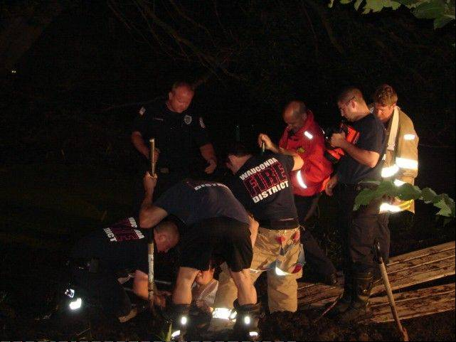 Rescue crews pull a 57-year-old Wauconda woman from mud late Monday night. She was struck up to her shoulders in the swampy mud.