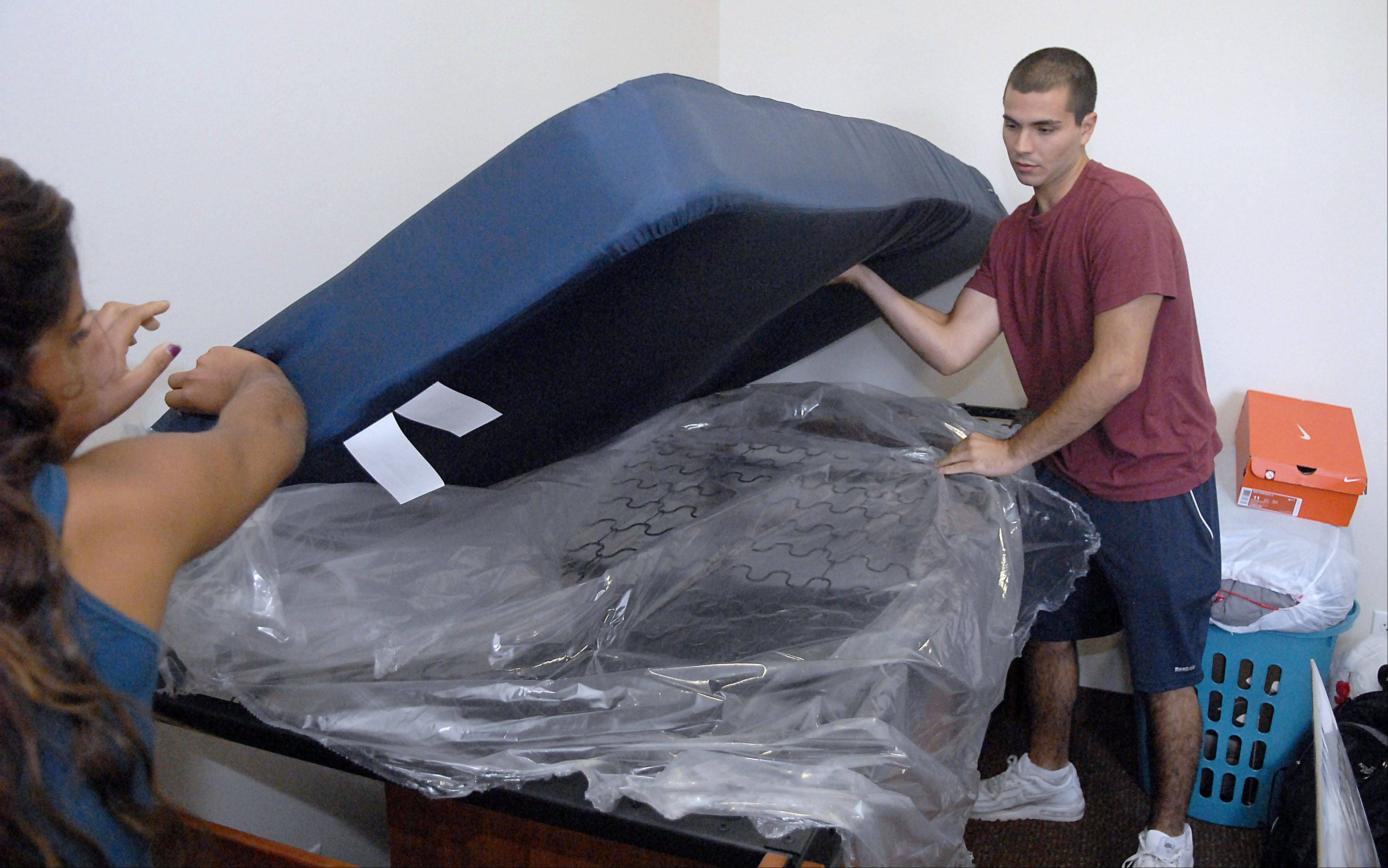 Freshman Santino Chiappetta of Hinsdale get helps from sister, Francesca, as he takes off the plastic covering of his new bed in his room at New Residence Hall West at Northern Illinois University in DeKalb on Thursday.