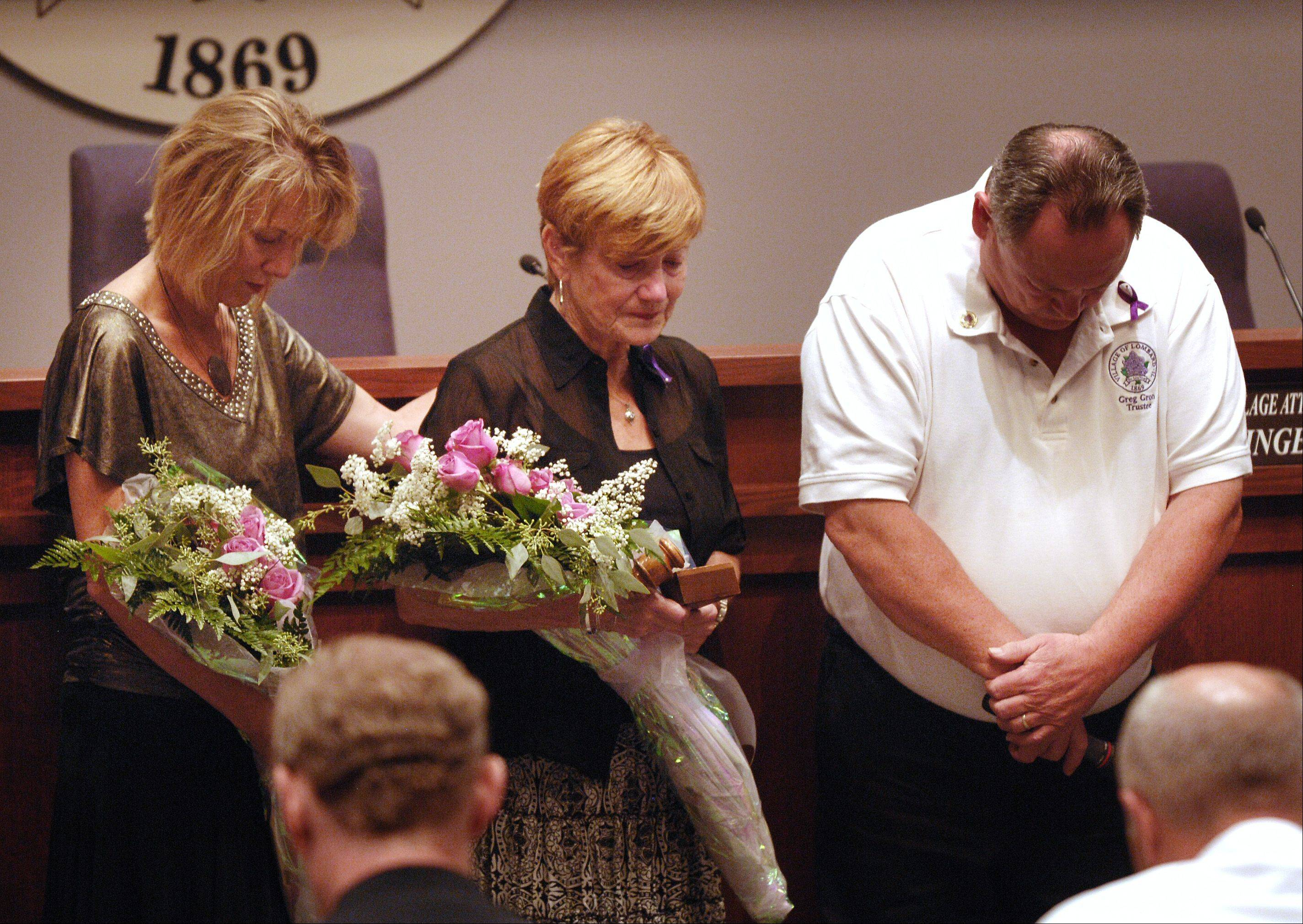 Donna Fruehe, daughter, Eileen Mueller, wife, and Lombard President Pro Tem Greg Gron honor the late Village President President Bill Mueller, who died Aug. 18, during a moment of silence on Thursday.
