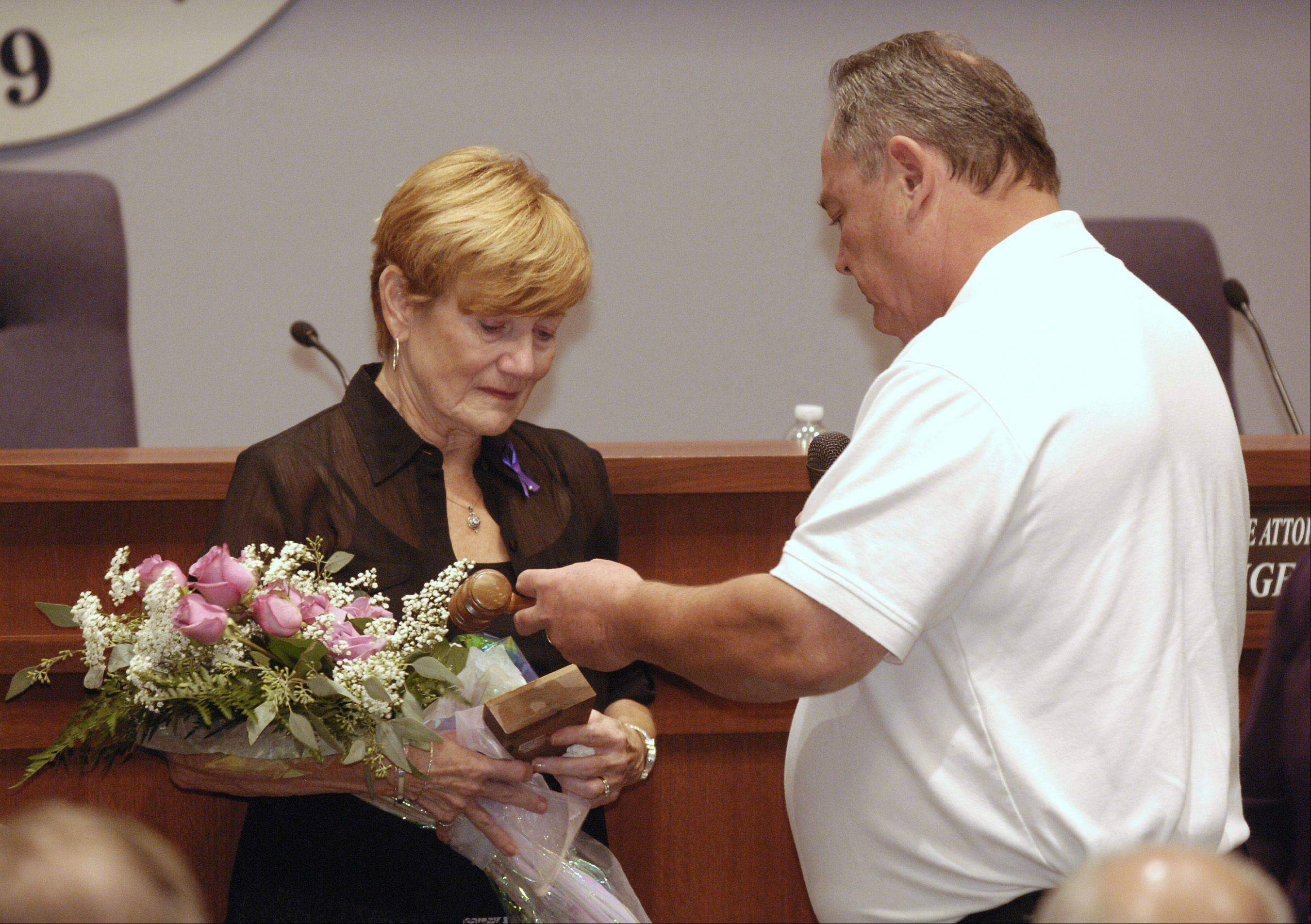Eileen Mueller receives her late husband Bill's gavel from Lombard President Pro Tem Greg Gron during the first village board meeting since Bill Mueller's death.
