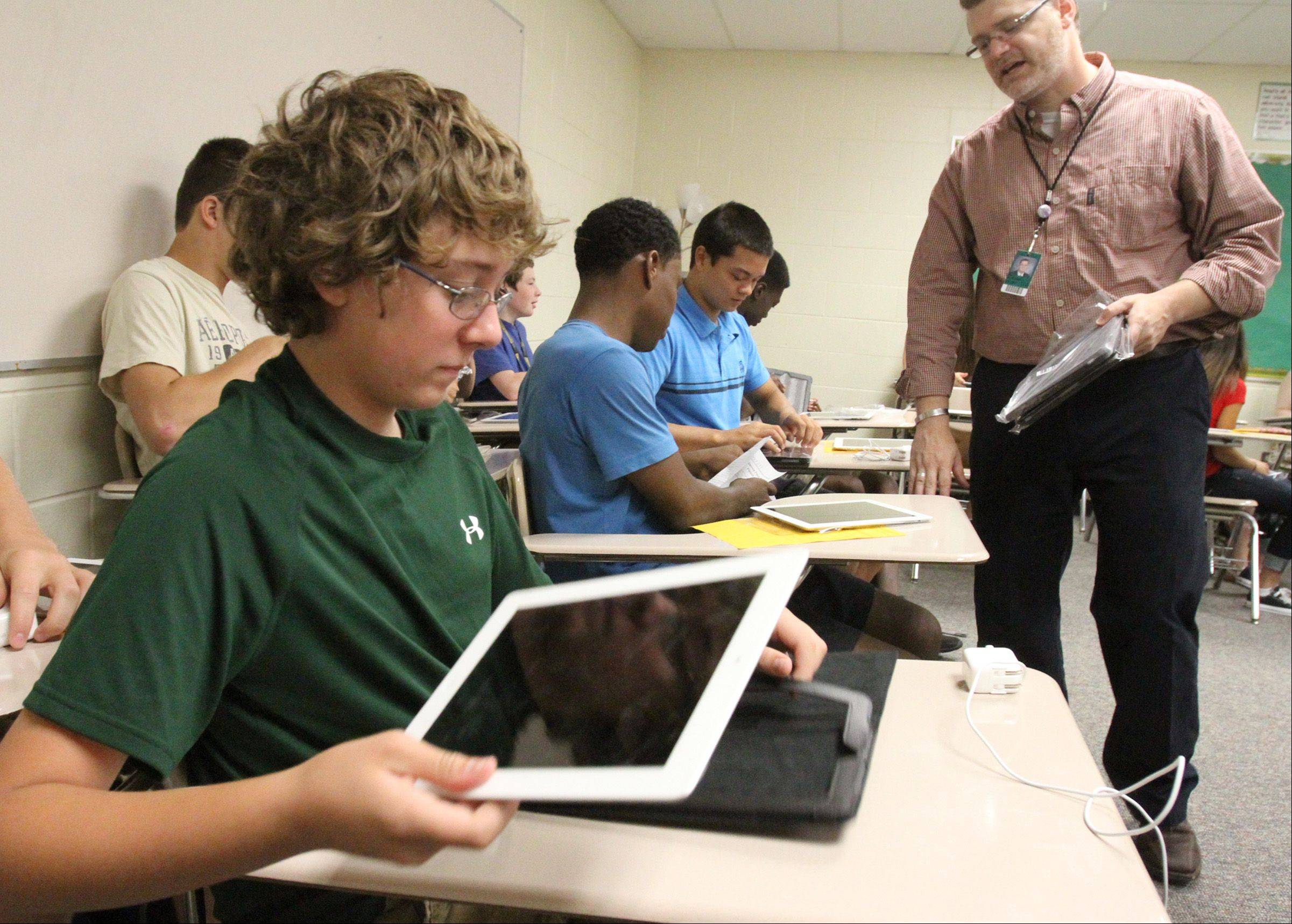 Fremd High School freshman Zach Kuehn places his new iPad in a case during social studies class with teacher Shawn McCusker as 300 students at the high school were issued iPads on the first day of school in Palatine on Thursday.